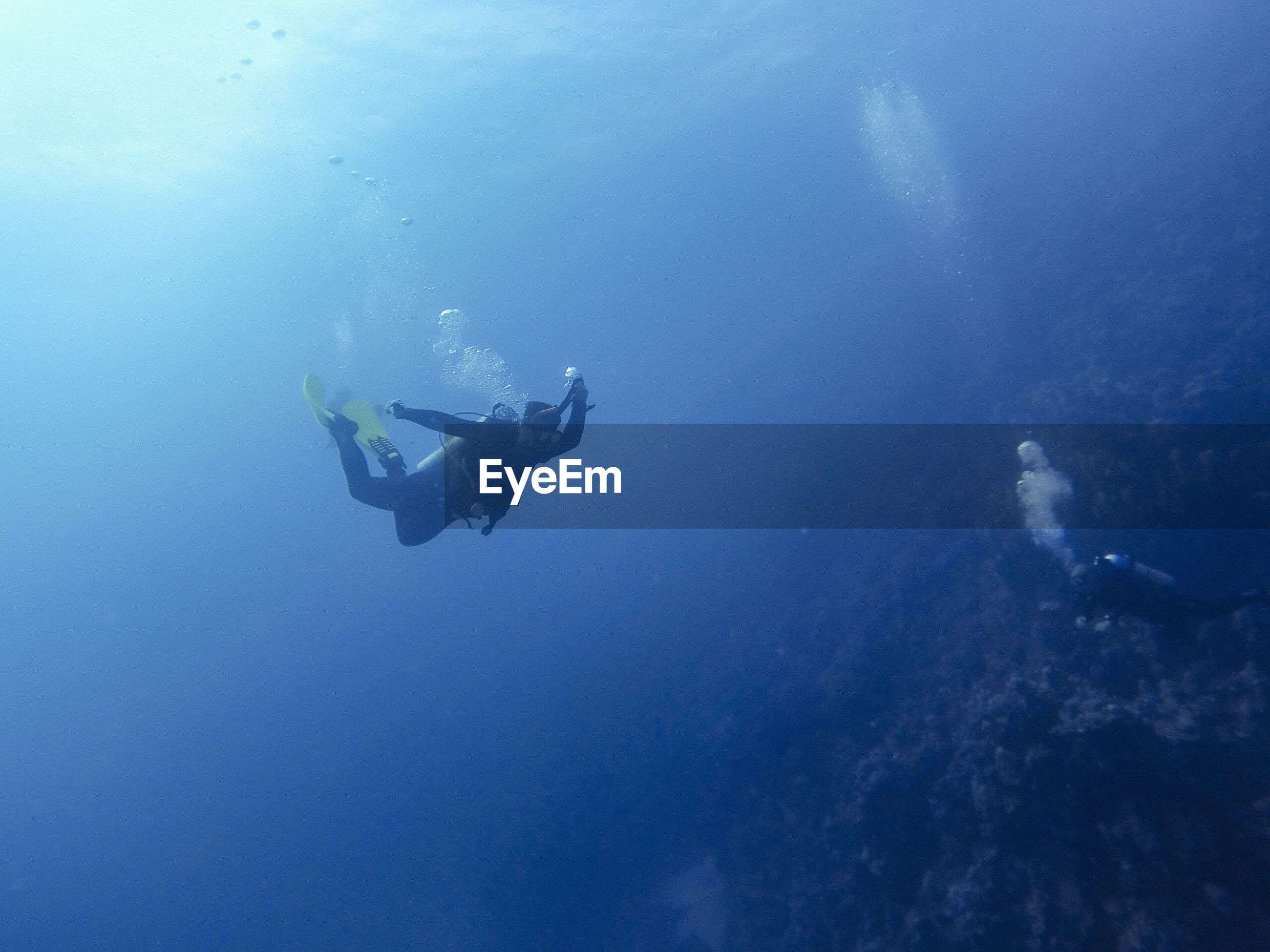 Scuba divers swimming through blue ocean
