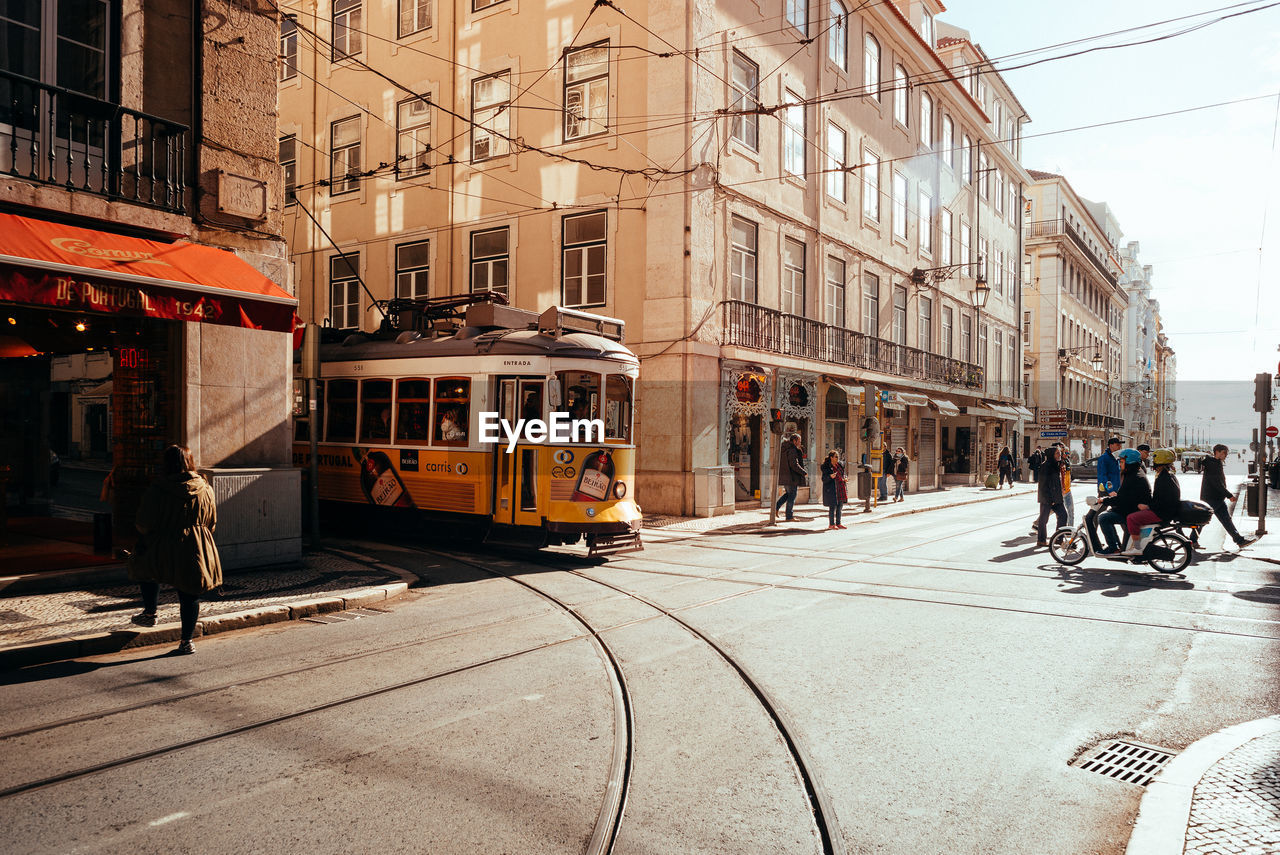 building exterior, architecture, city, built structure, transportation, street, mode of transportation, cable car, incidental people, building, railroad track, track, day, sunlight, city street, rail transportation, group of people, public transportation, land vehicle, road, outdoors