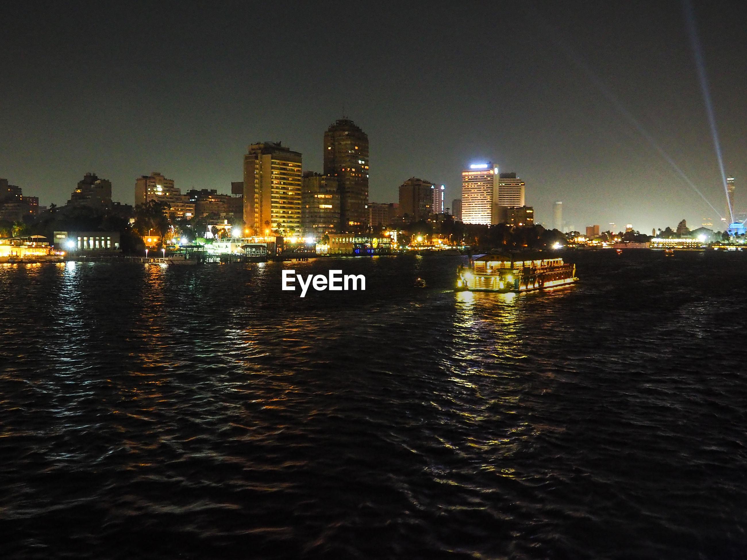 ILLUMINATED BUILDINGS BY SEA AT NIGHT