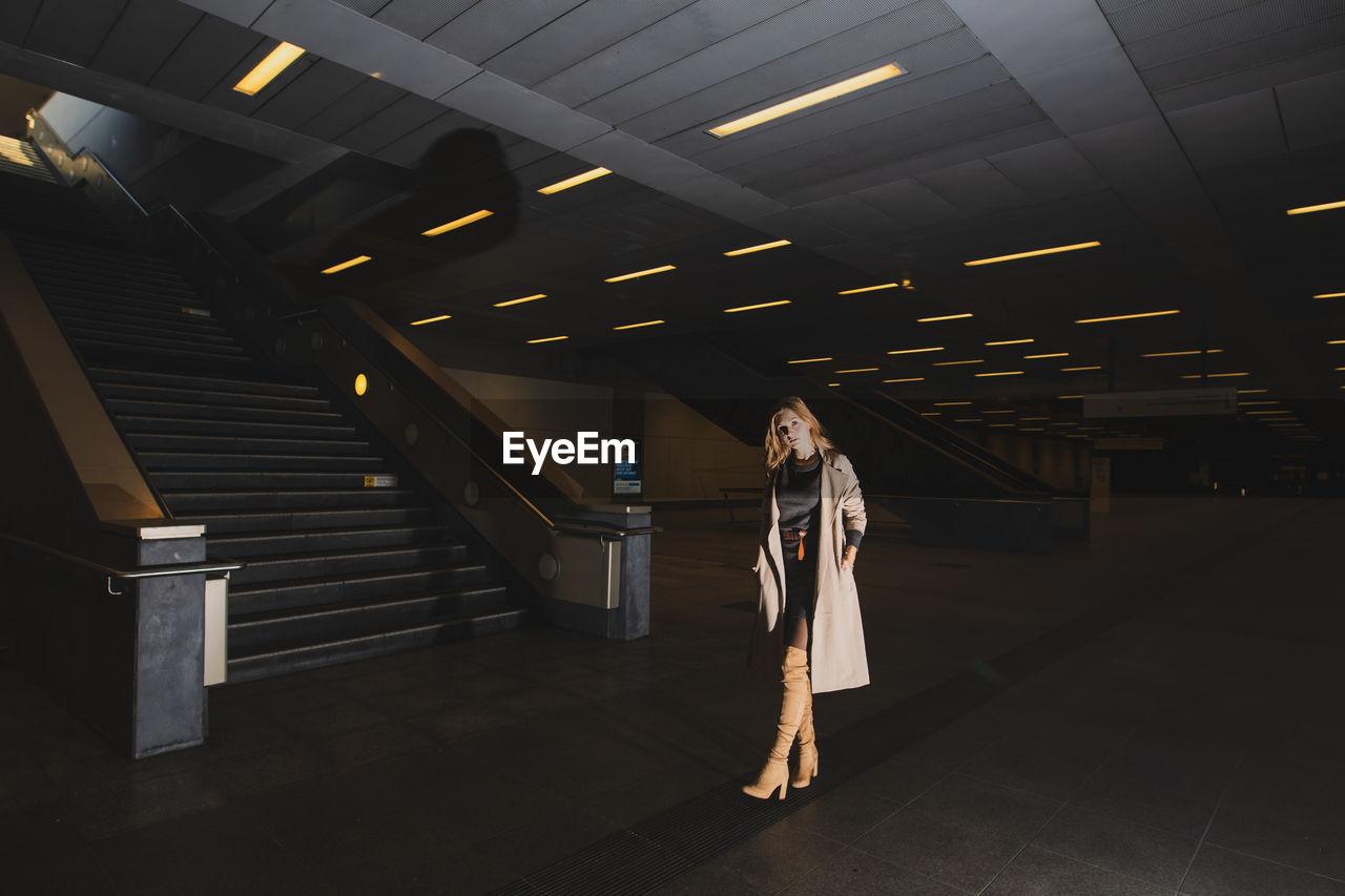 Woman Standing In Illuminated Subway