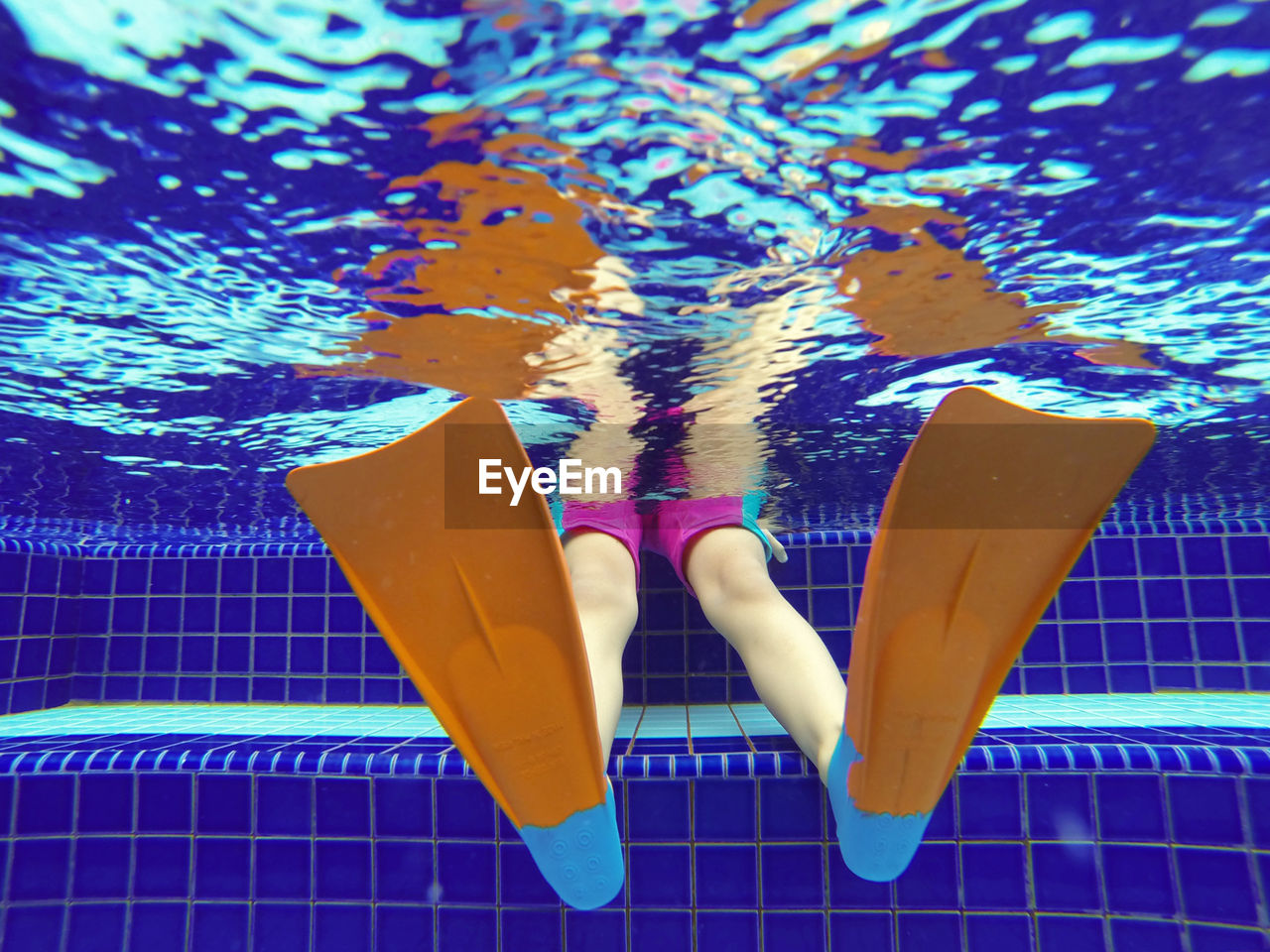 Low angle view of person wearing diving flipper in swimming pool