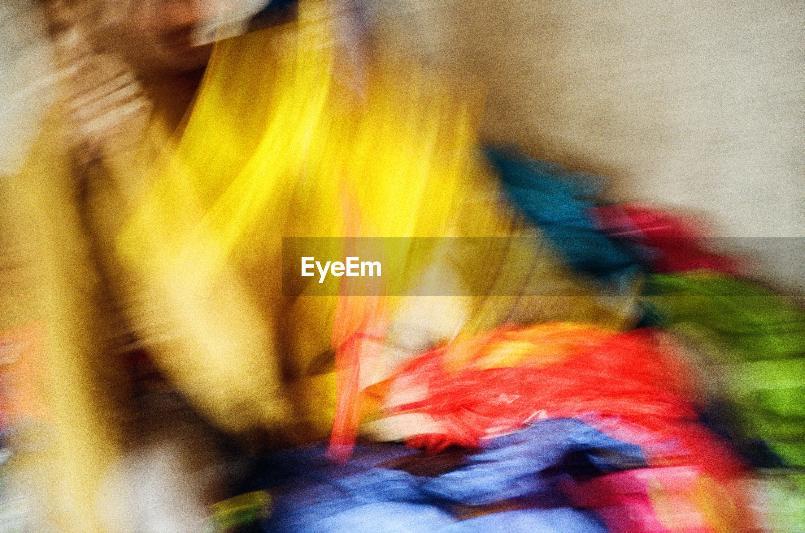 Blurred motion of person with multi colored fabric