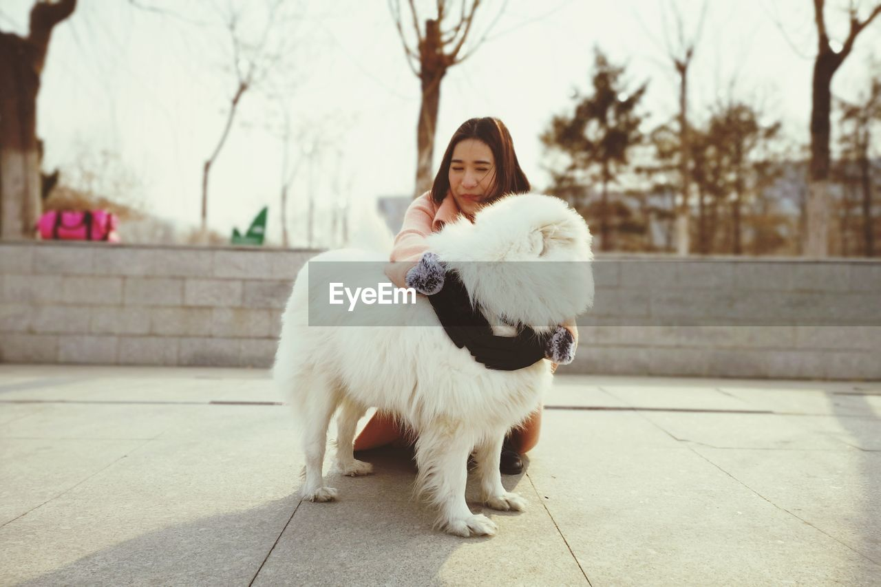 Young woman embracing dog outdoors