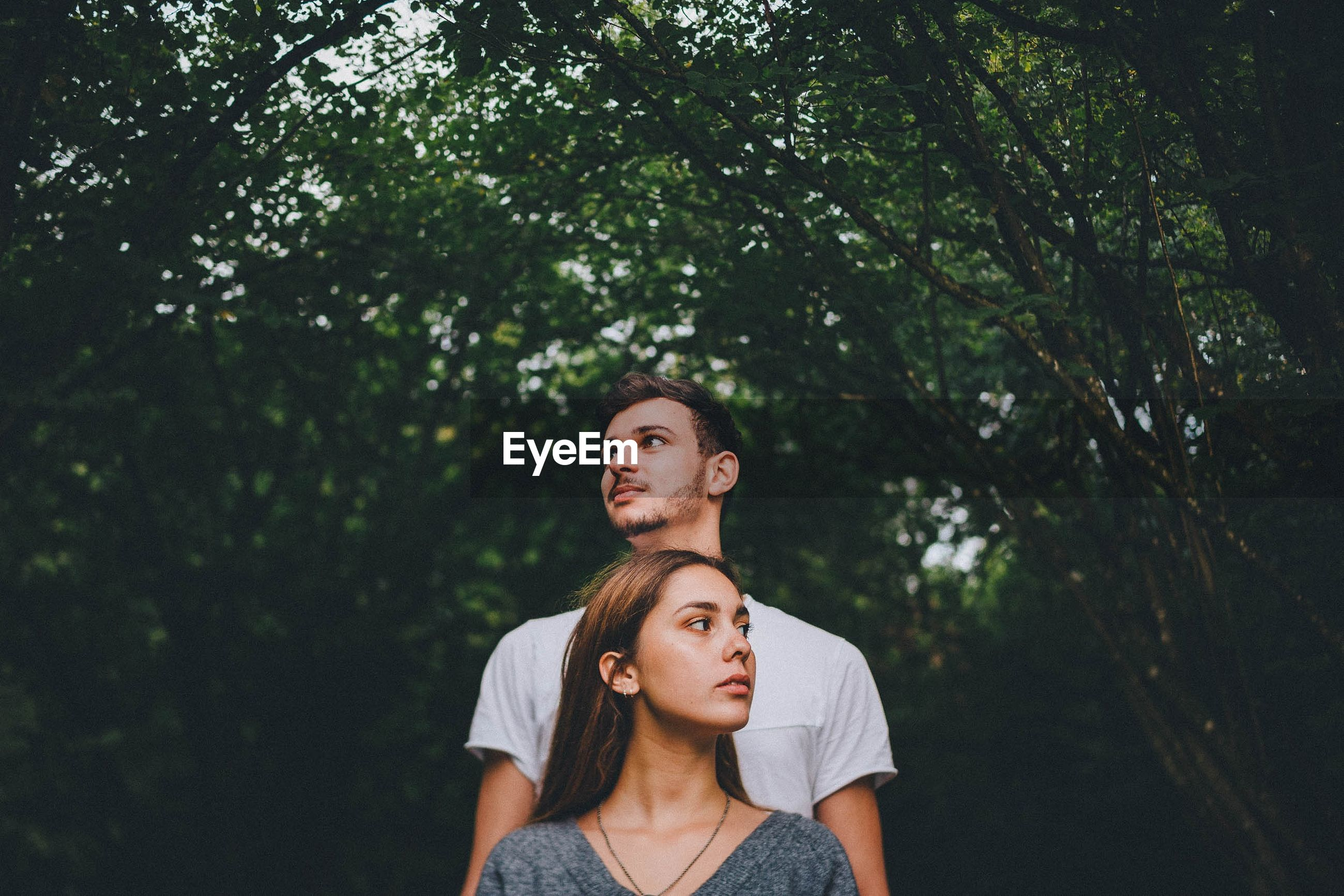 two people, real people, tree, young adult, portrait, plant, togetherness, front view, lifestyles, couple - relationship, day, casual clothing, people, headshot, leisure activity, looking, focus on foreground, young women, nature, young men, contemplation