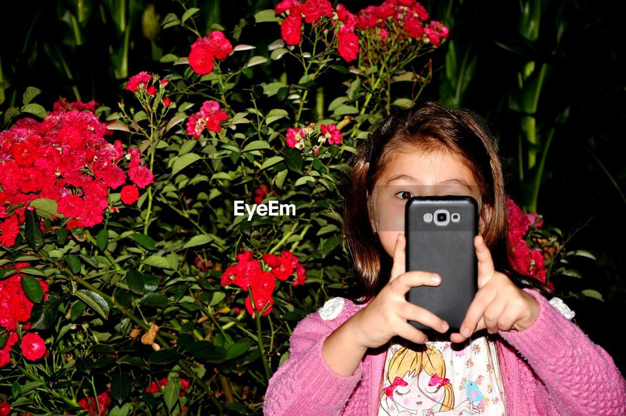 Girl Photographing By Flowers From Mobile Phone