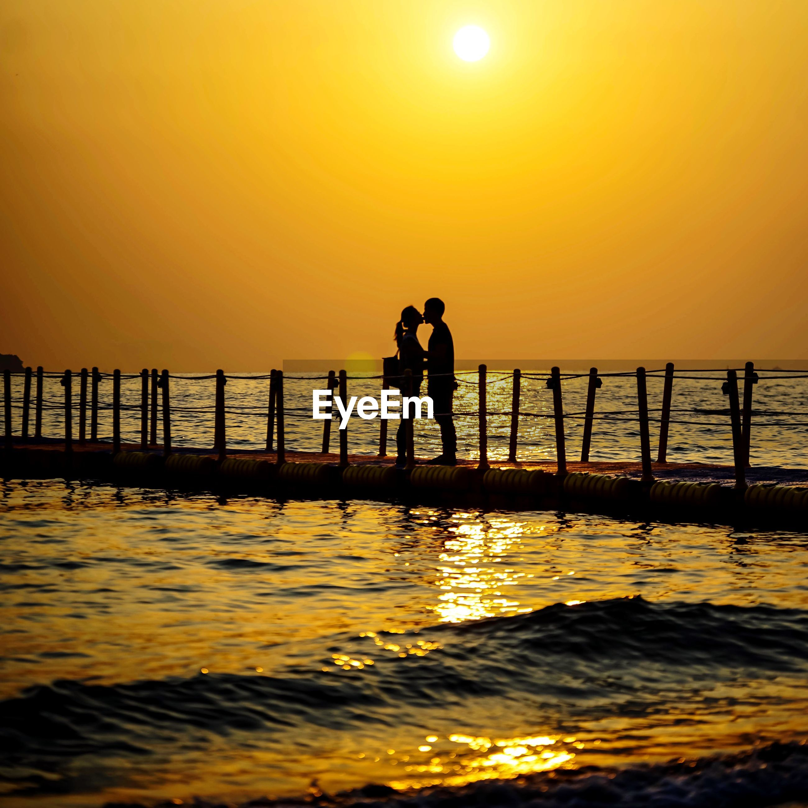 Silhouette couple kissing while standing on pier over sea against orange sky during sunset