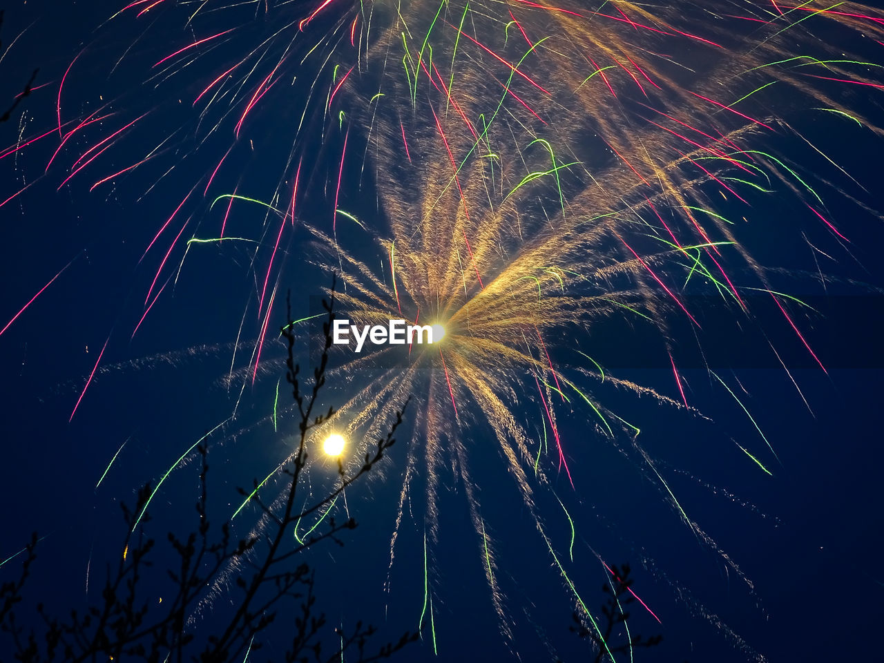 Low Angle View Of Colorful Fireworks Exploding Against Clear Sky At Night