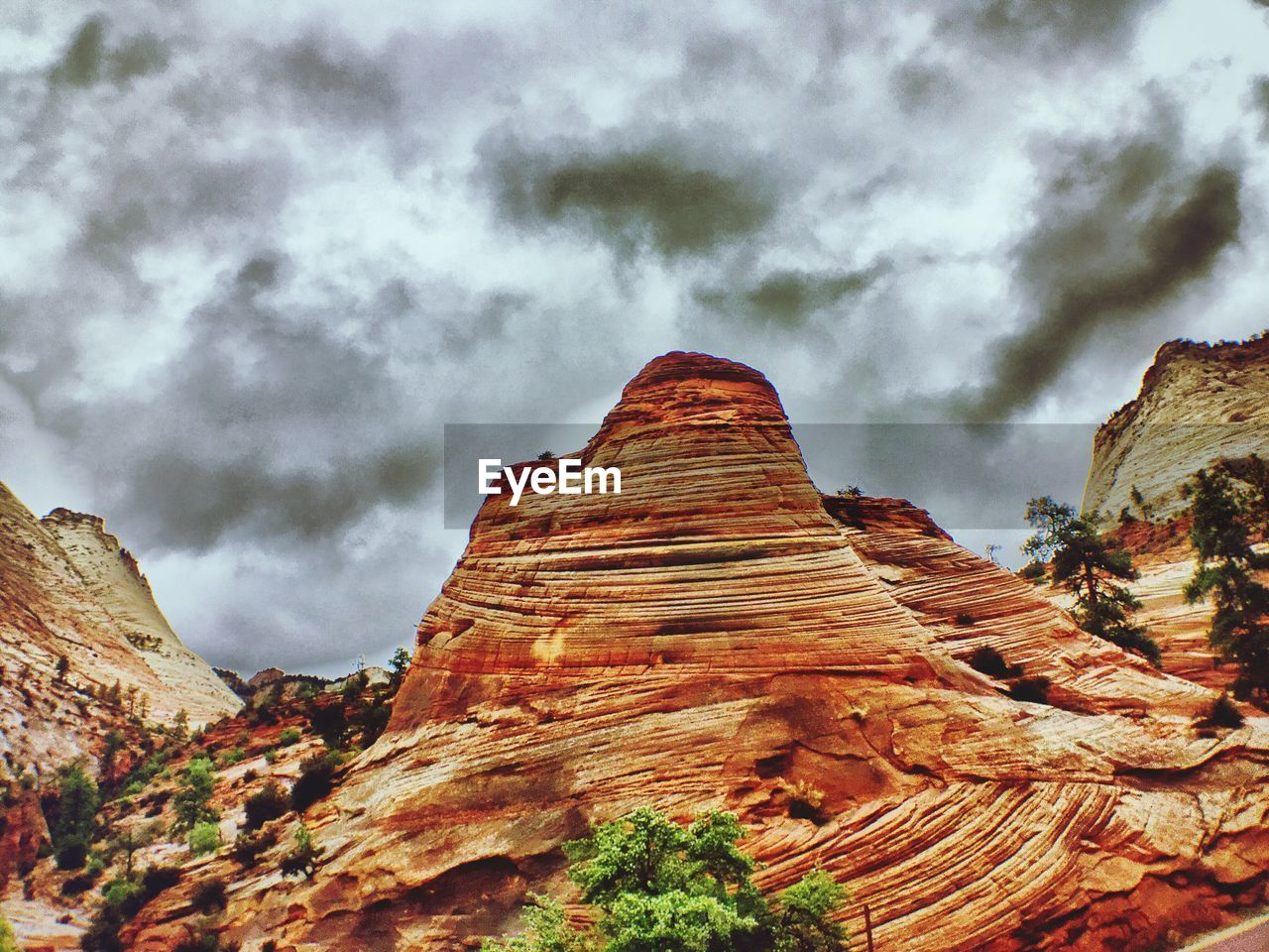 Low angle view of rocky mountains against cloudy sky at zion national park