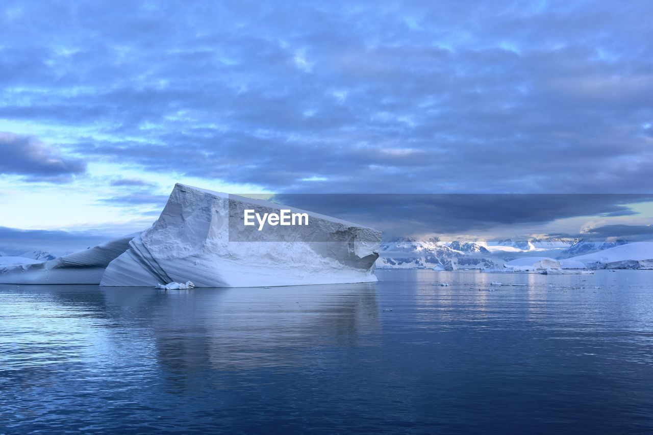 Scenic view of glaciers in sea against sky