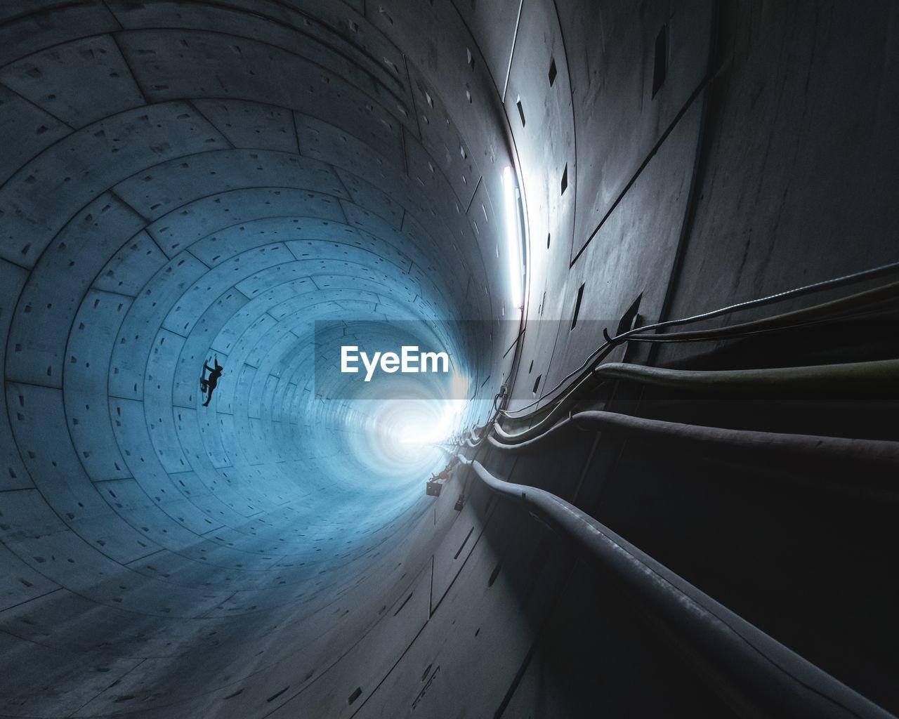Silhouette Man Working In Illuminated Tunnel