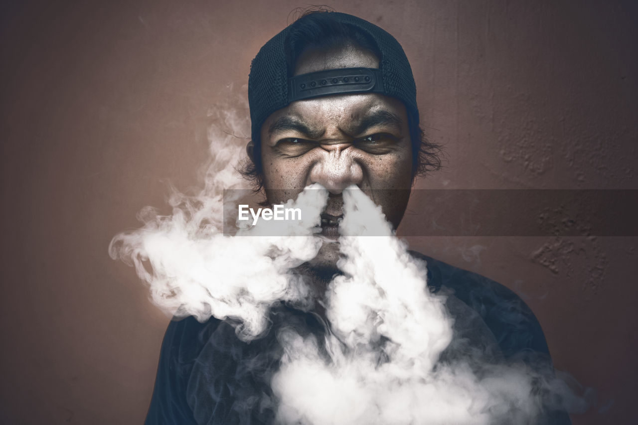 Portrait of man exhaling smoke against wall