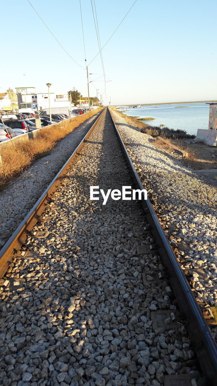 transportation, sky, rail transportation, track, nature, railroad track, diminishing perspective, gravel, solid, stone - object, direction, no people, day, the way forward, rock, vanishing point, water, pebble, sunlight, clear sky, surface level, outdoors, long