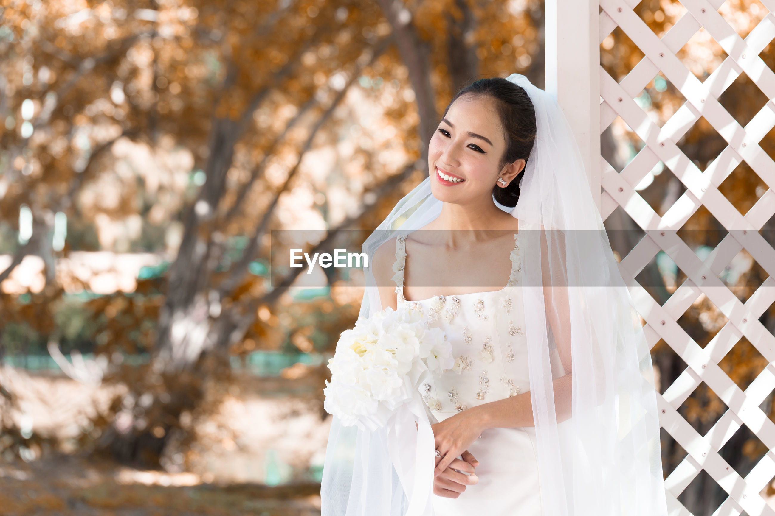 Smiling bride holding bouquet looking away