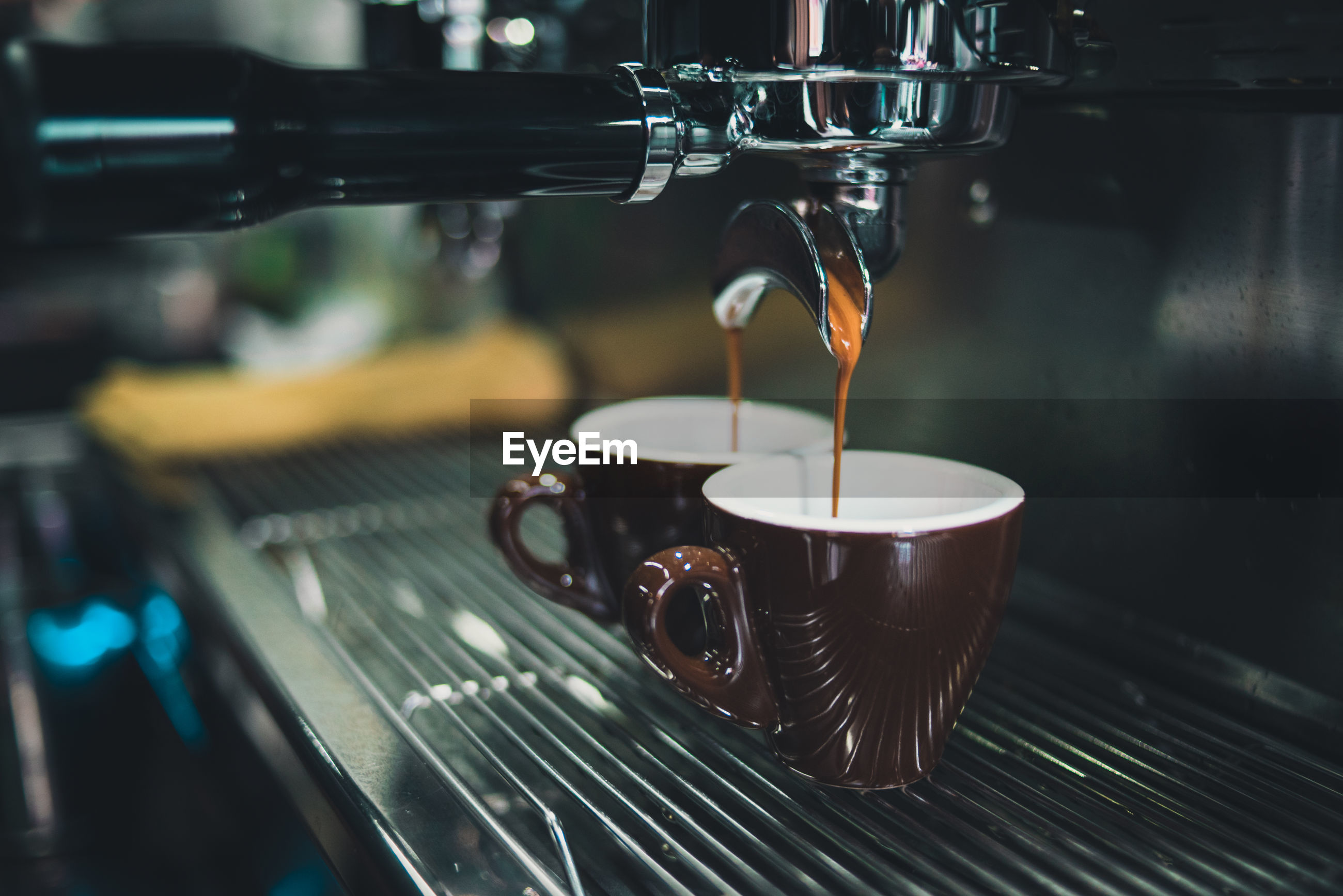Close-up of coffee cup on espresso maker in cafe
