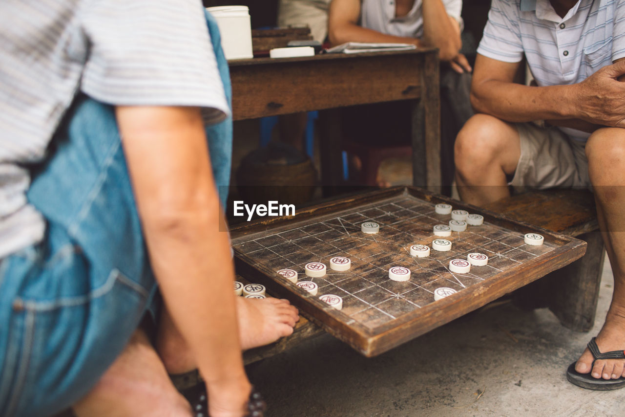 Low section of men playing board game outdoors