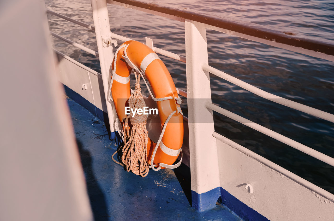 High angle view of lifebelt tied to railing of boat