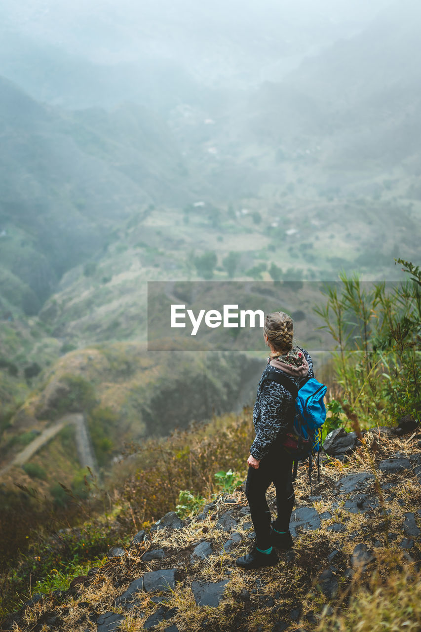 High Angle View Of Backpacker Looking At View While Standing On Mountain