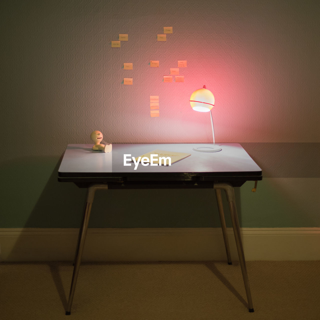 Table With Lamp And Adhesive Notes On Wall