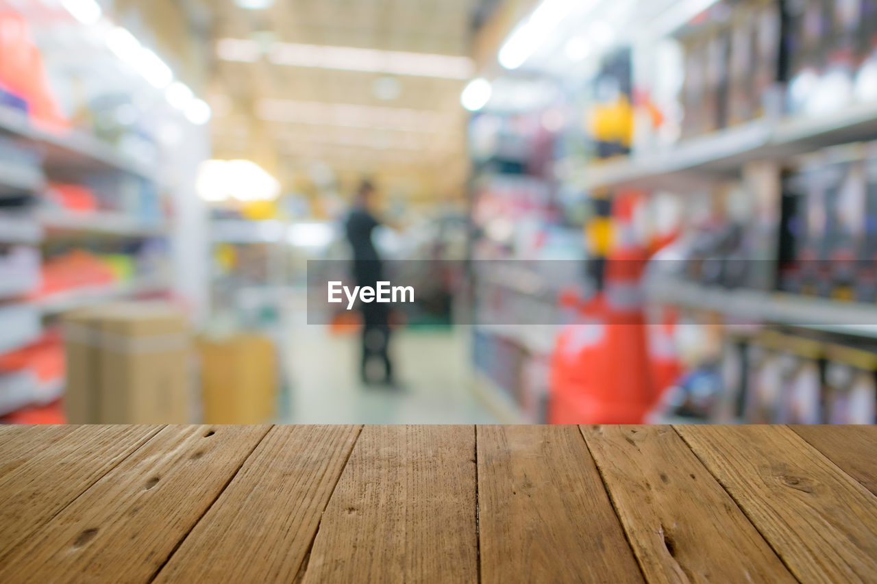 indoors, wood - material, focus on foreground, one person, retail, store, real people, incidental people, supermarket, selective focus, lifestyles, shelf, architecture, shopping, men, day, flooring, empty, market, consumerism