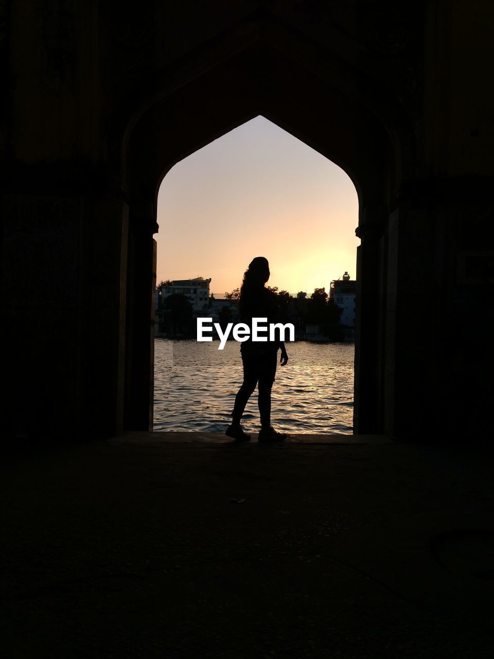 sunset, silhouette, full length, water, arch, real people, architecture, built structure, sky, lifestyles, women, nature, outdoors, one person, beauty in nature, day, people