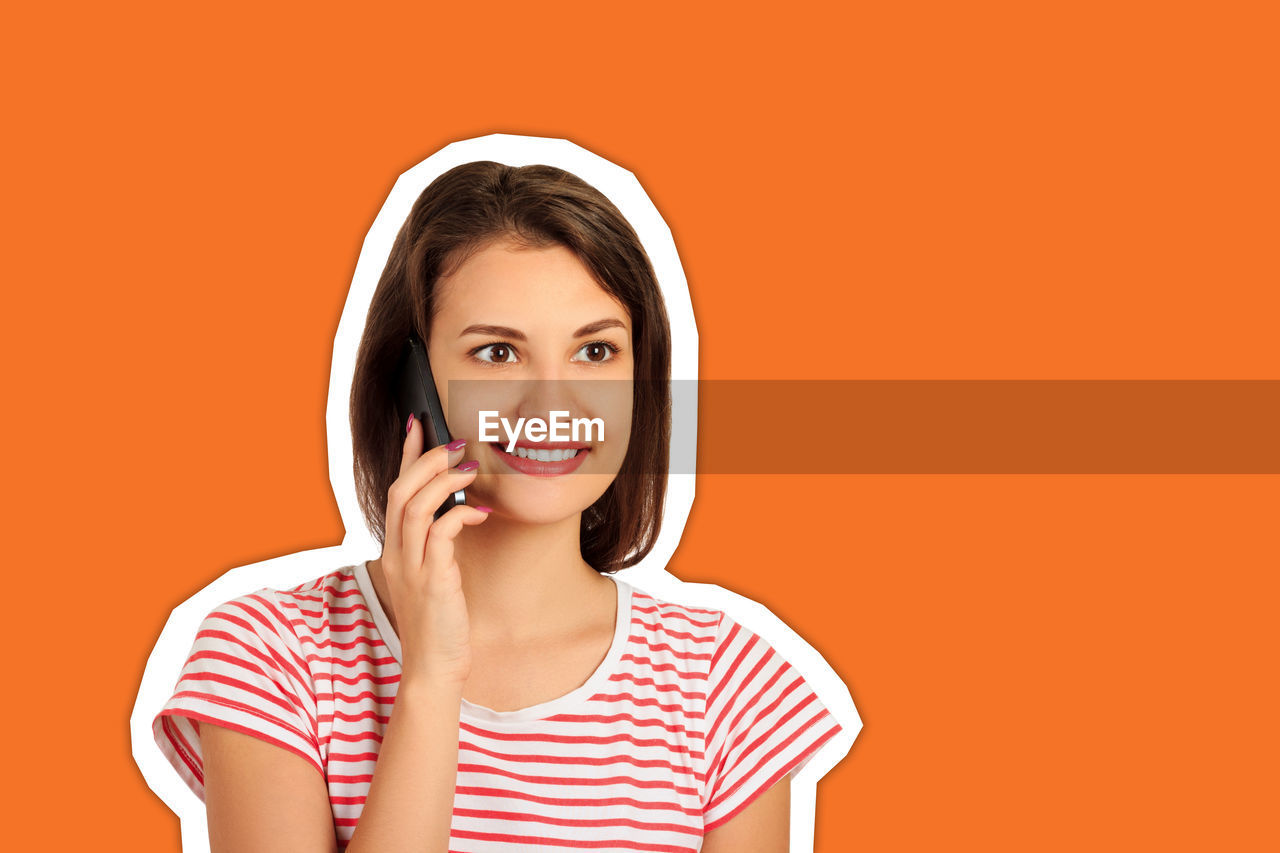 Smiling young woman talking over mobile phone cut out against orange background