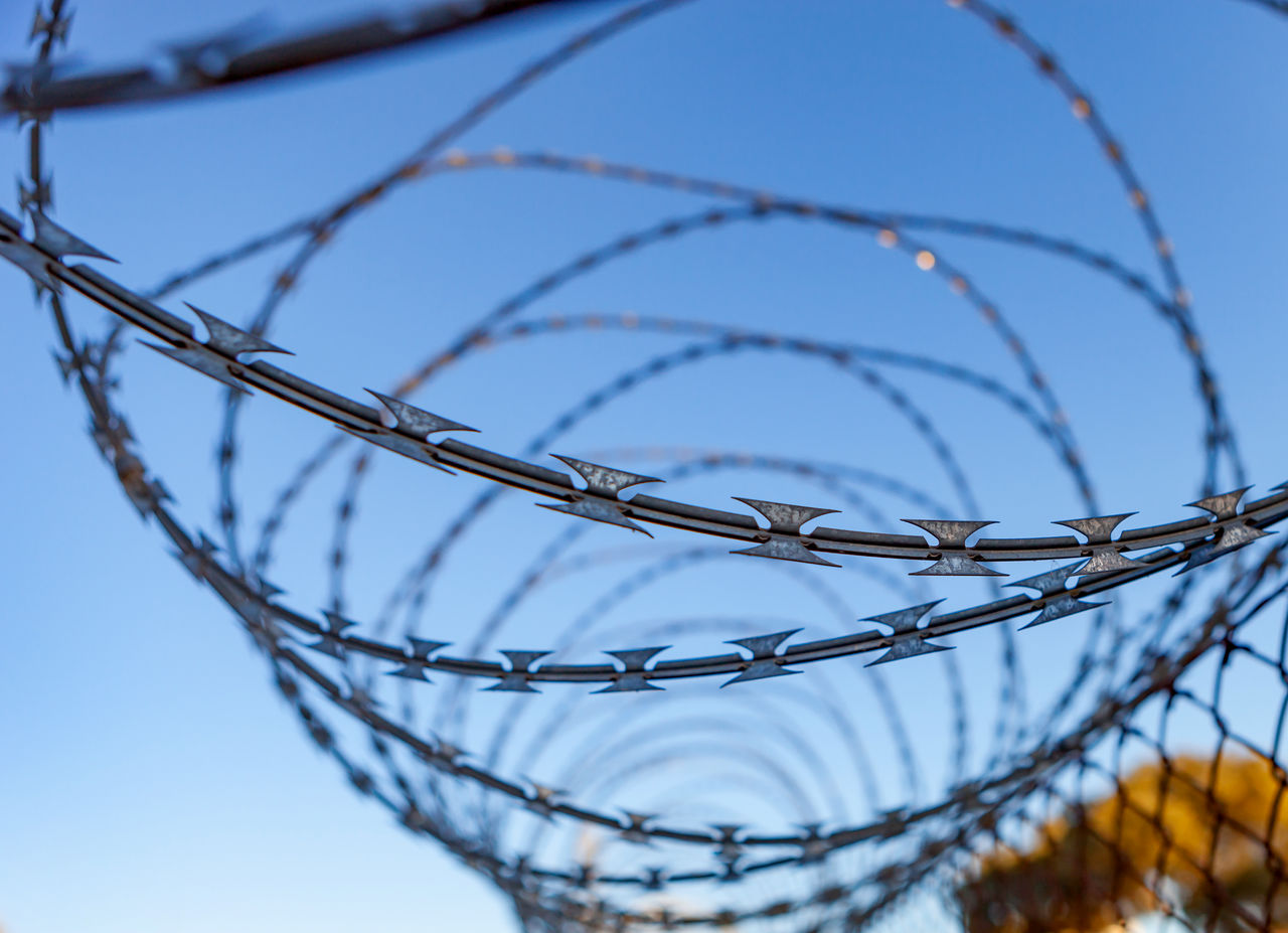 fence, metal, security, razor wire, protection, boundary, barrier, safety, barbed wire, wire, sky, sharp, selective focus, no people, low angle view, warning sign, sign, day, close-up, spiral, outdoors