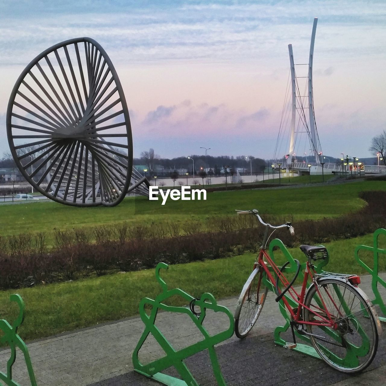 grass, transportation, mode of transport, outdoors, sky, green color, no people, bicycle, day, ferris wheel, stationary, building exterior, land vehicle, architecture, nature, cloud - sky, built structure, travel destinations, water, beauty in nature