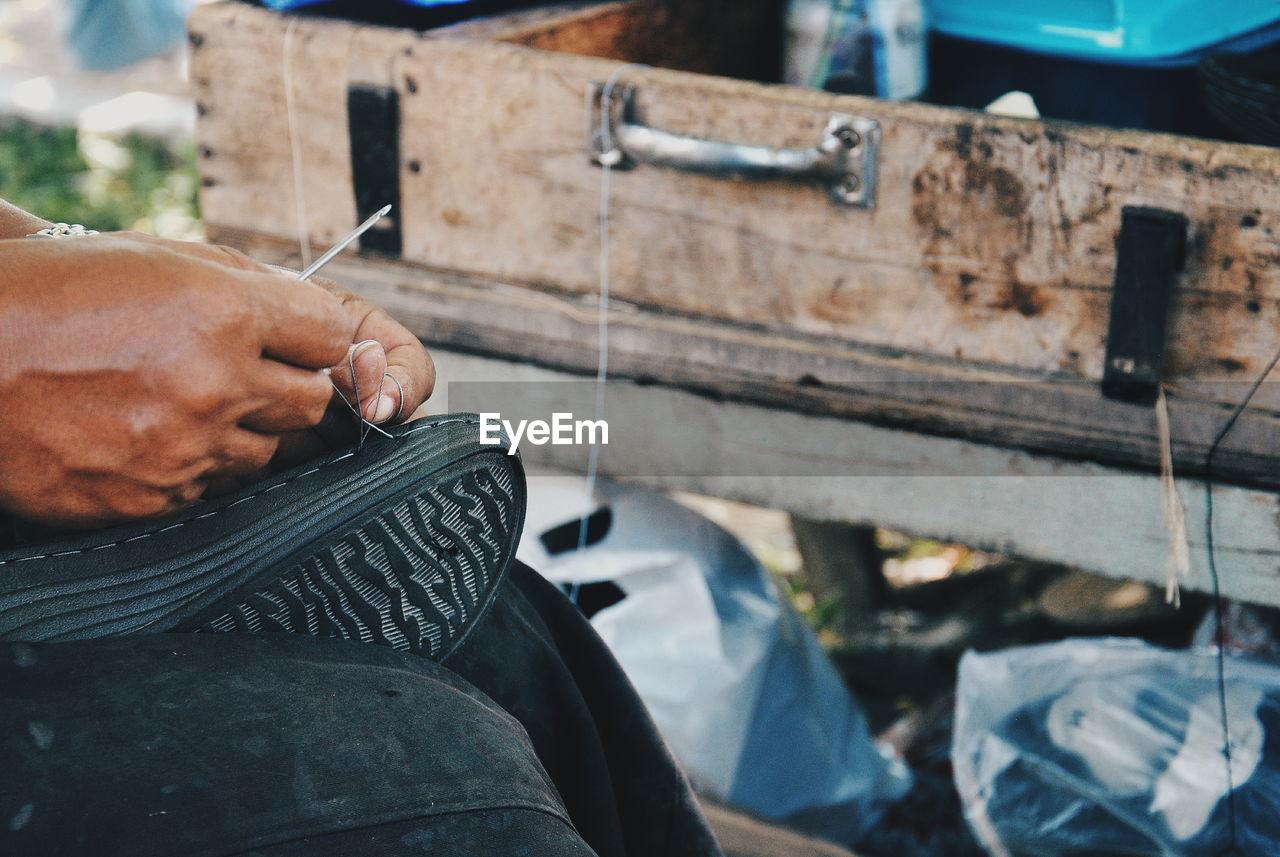Cropped Image Of Man Repairing Shoe