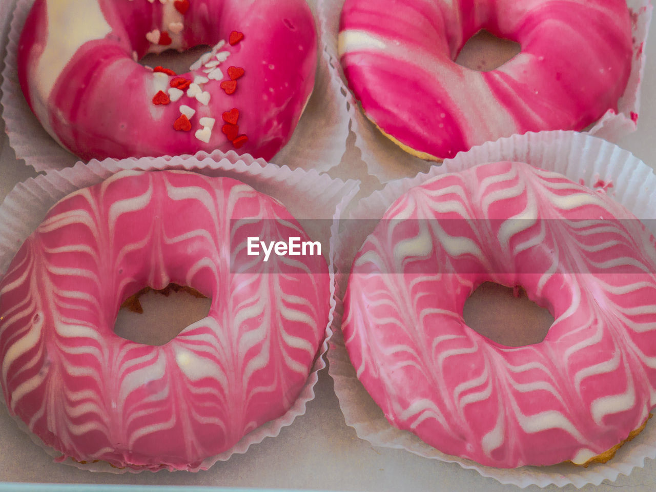 food and drink, food, freshness, sweet food, indulgence, baked, still life, sweet, temptation, ready-to-eat, close-up, dessert, unhealthy eating, indoors, no people, high angle view, pink color, donut, table, red, snack