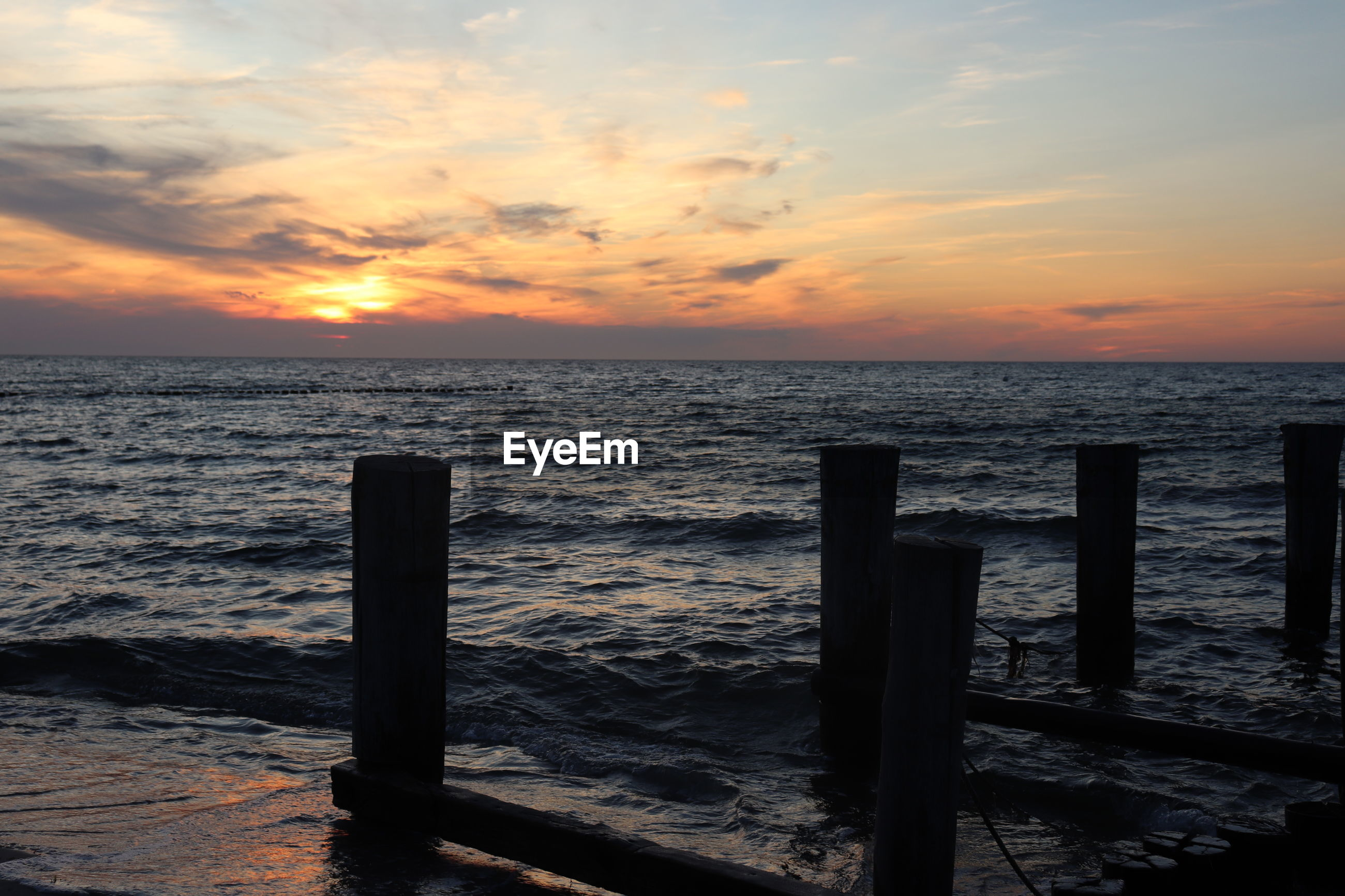 WOODEN POSTS ON SEA AGAINST SKY DURING SUNSET