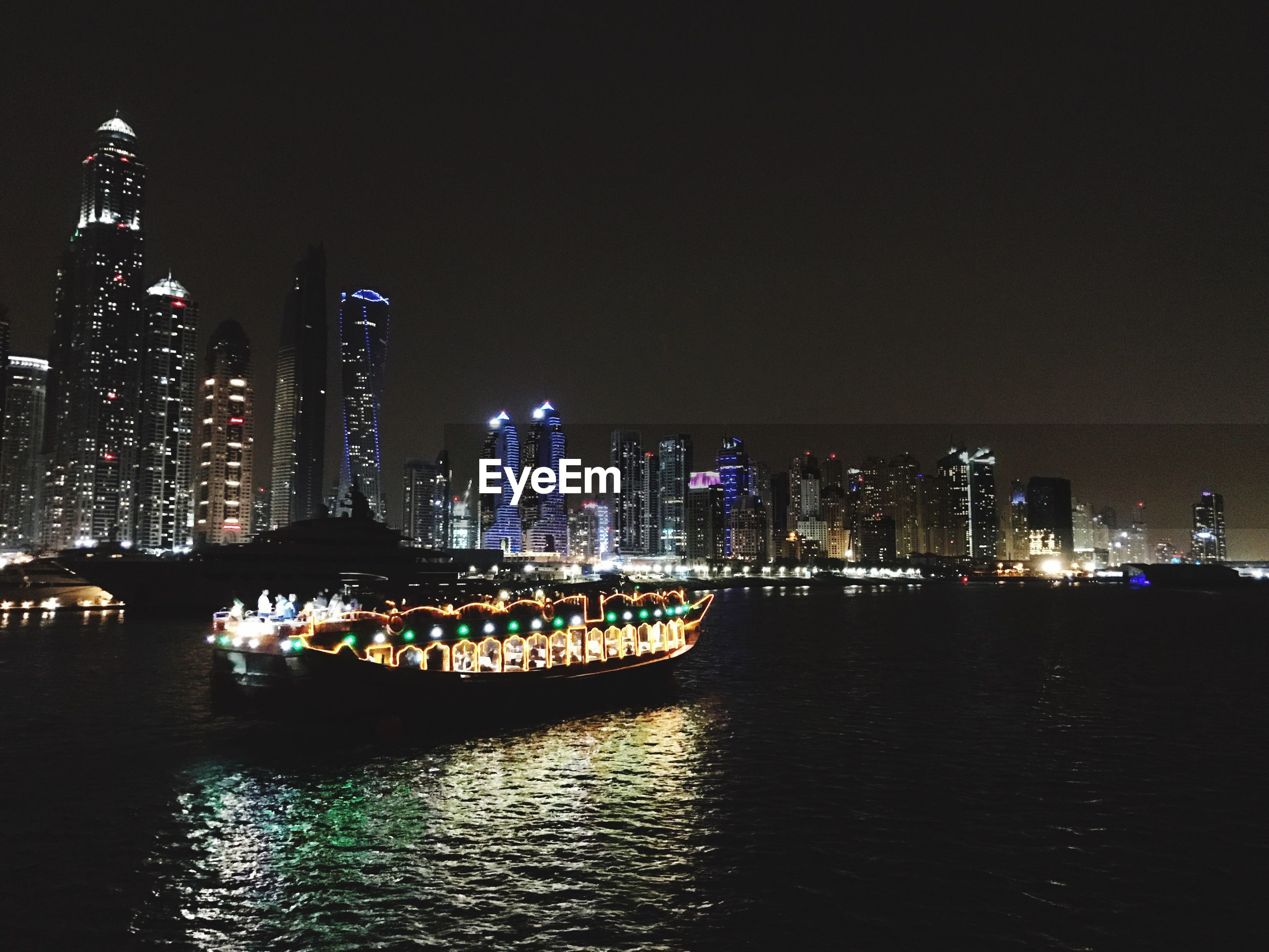 Illuminated ferry moving on sea by city at night