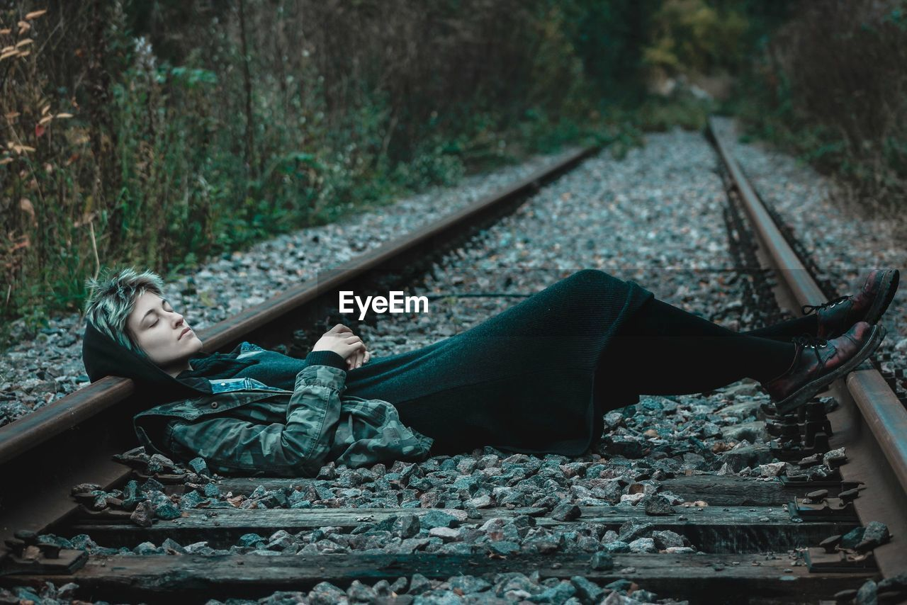 Young Woman Lying On Railroad Track