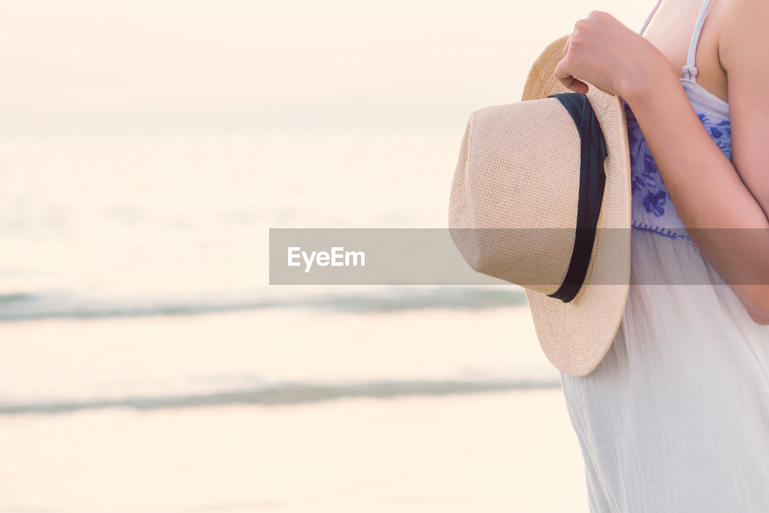 Midsection of pregnant woman holding sun hat at beach