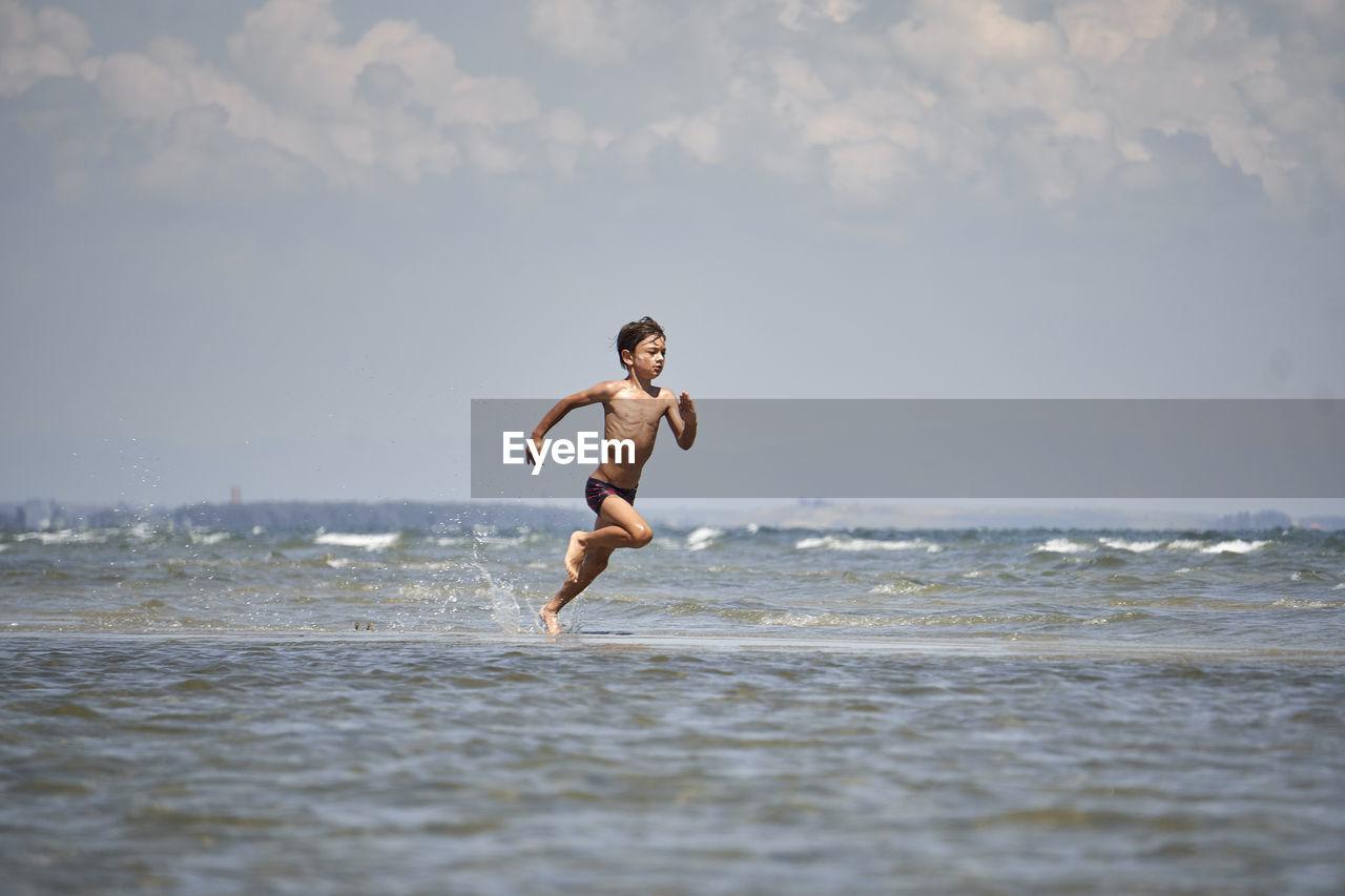 Full Length Of Shirtless Boy Running On Sea Against Sky