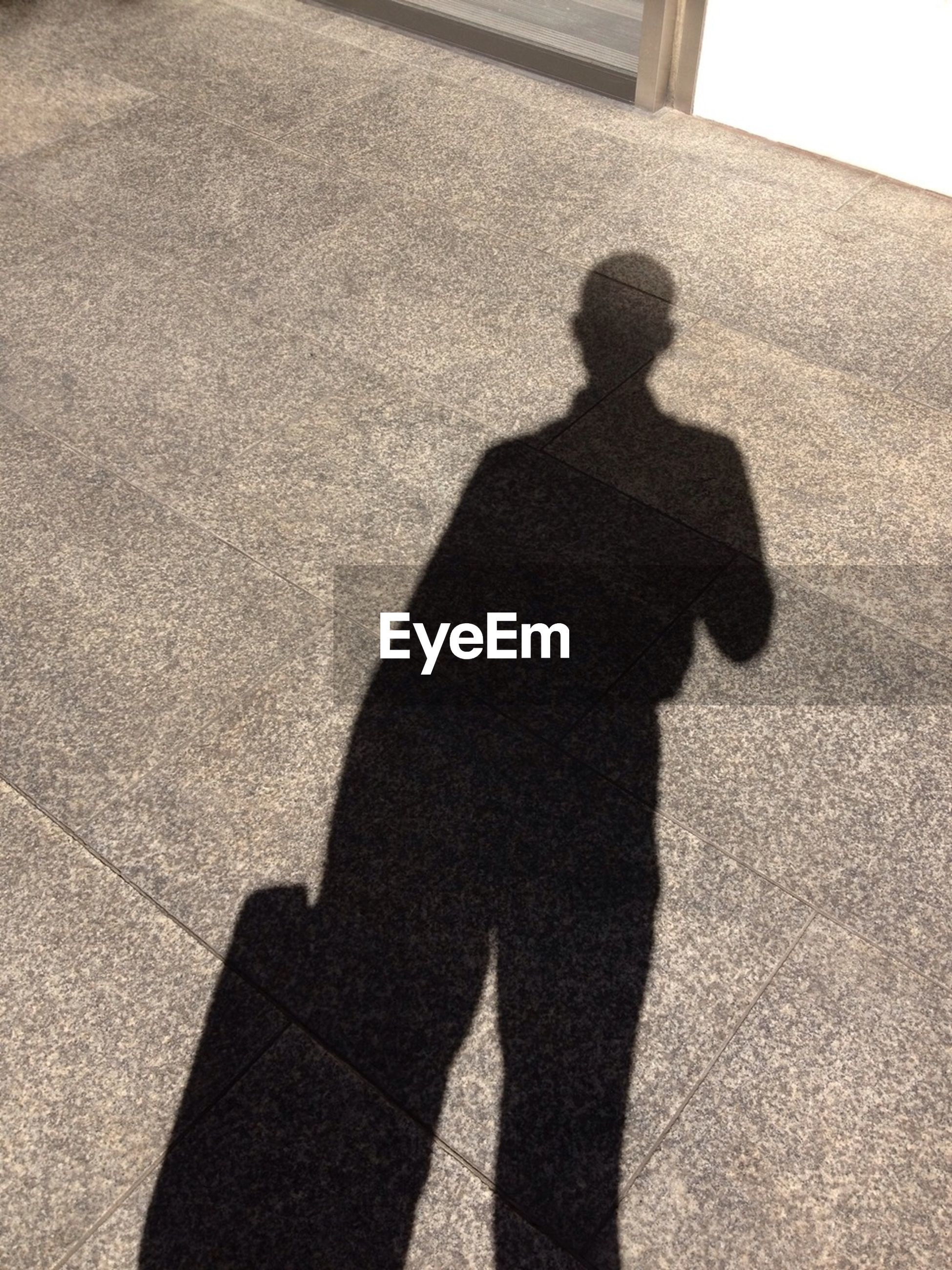 Shadow of man on street