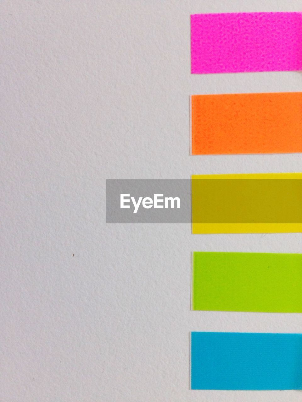 Close-Up Of Colorful Papers Stuck On White Wall