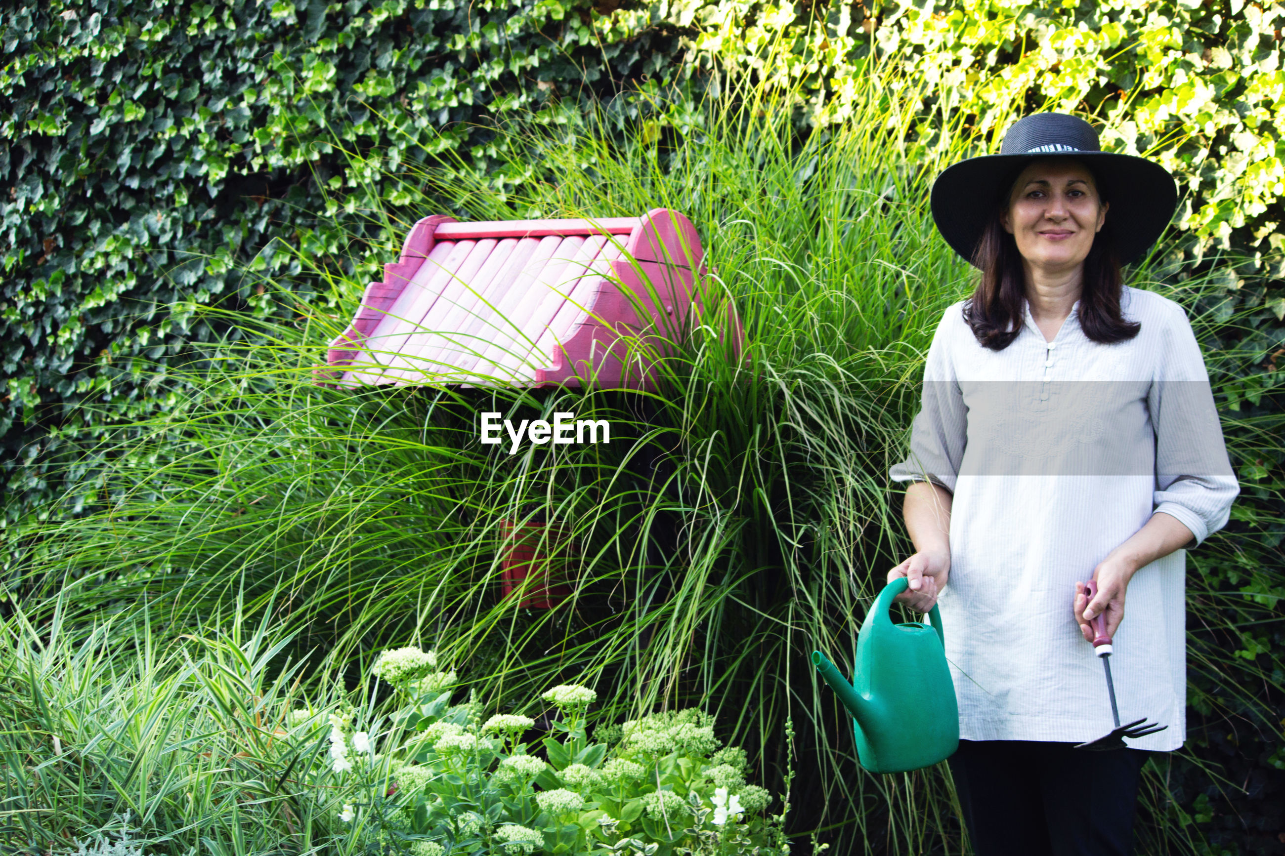 Portrait of woman holding equipment and can while standing by plants