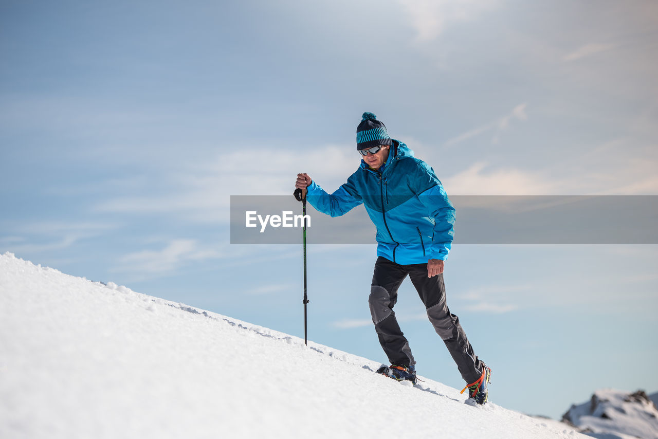 one person, sky, winter, leisure activity, cold temperature, sport, snow, cloud - sky, full length, lifestyles, winter sport, real people, day, nature, mountain, clothing, extreme sports, adult, warm clothing, outdoors