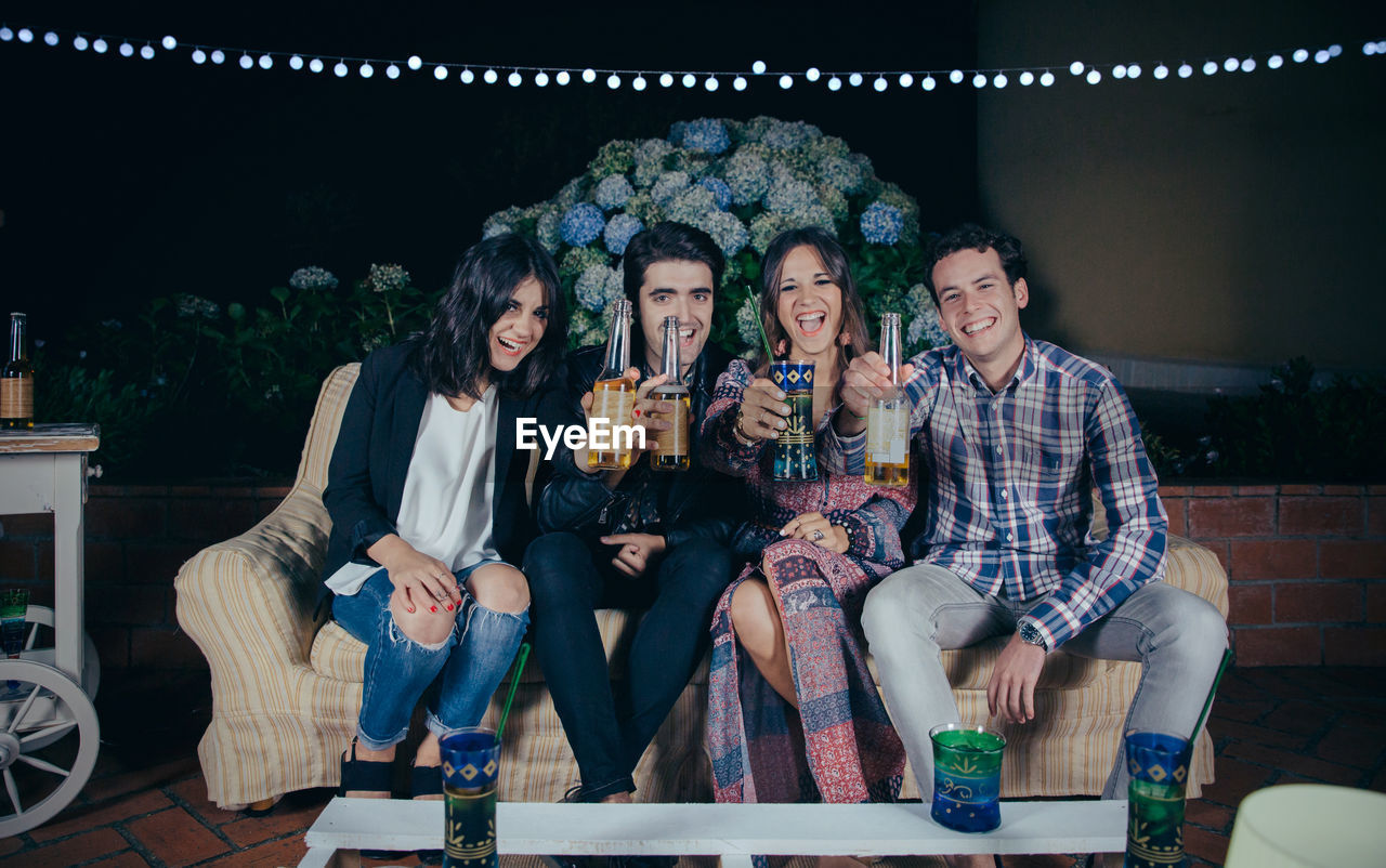 Portrait Of Friends Having Drink While Enjoying In Party At Night