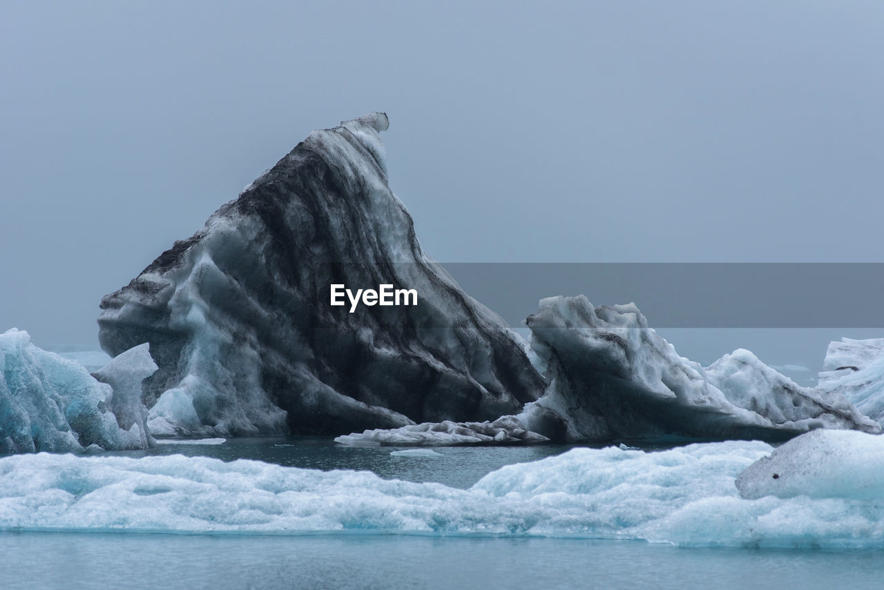 Scenic view of glaciers in sea against clear sky
