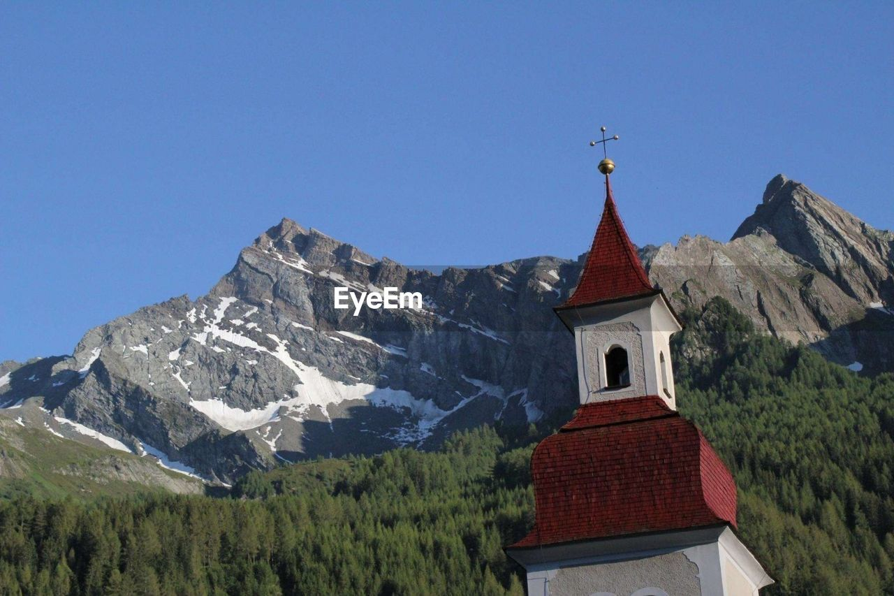 Low angle view of church and mountain against clear blue sky