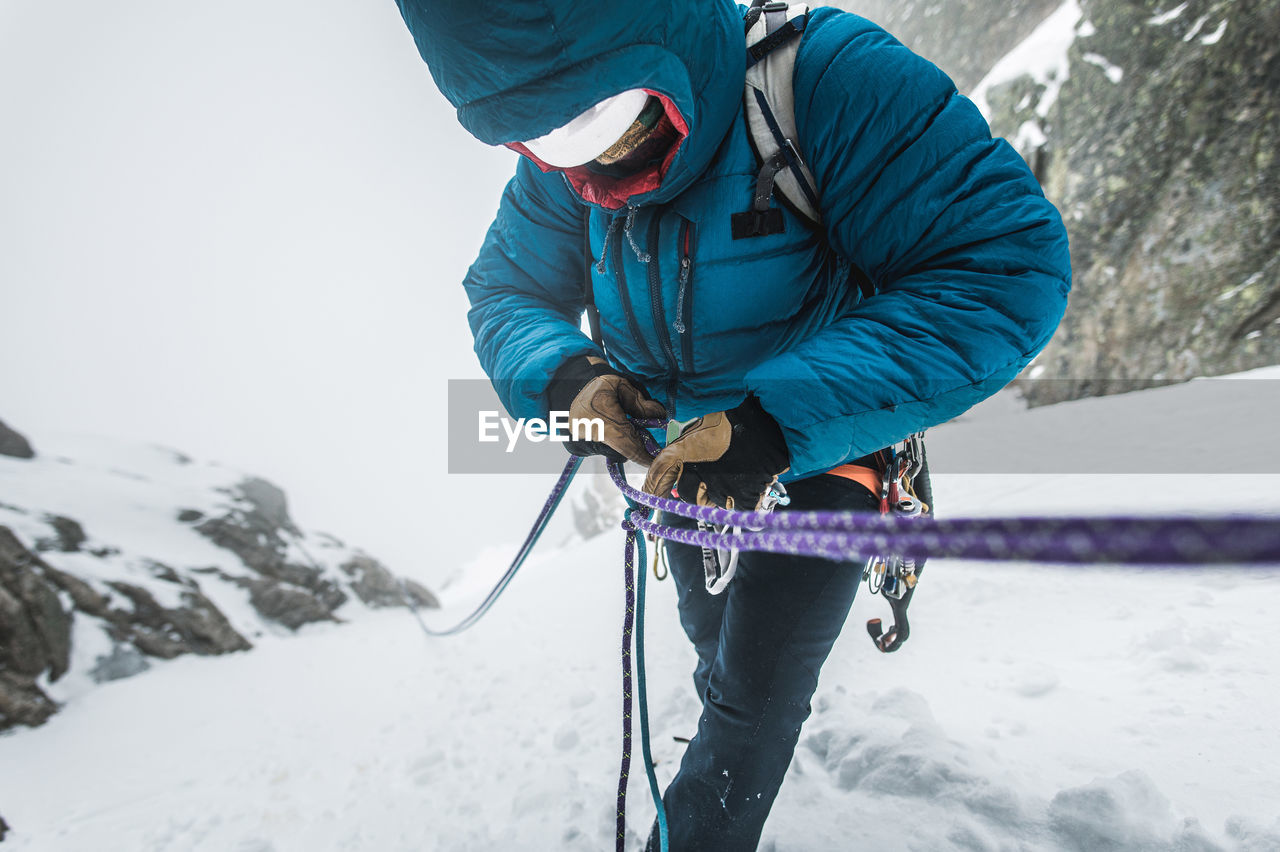 MAN CLIMBING ON SNOW COVERED MOUNTAIN
