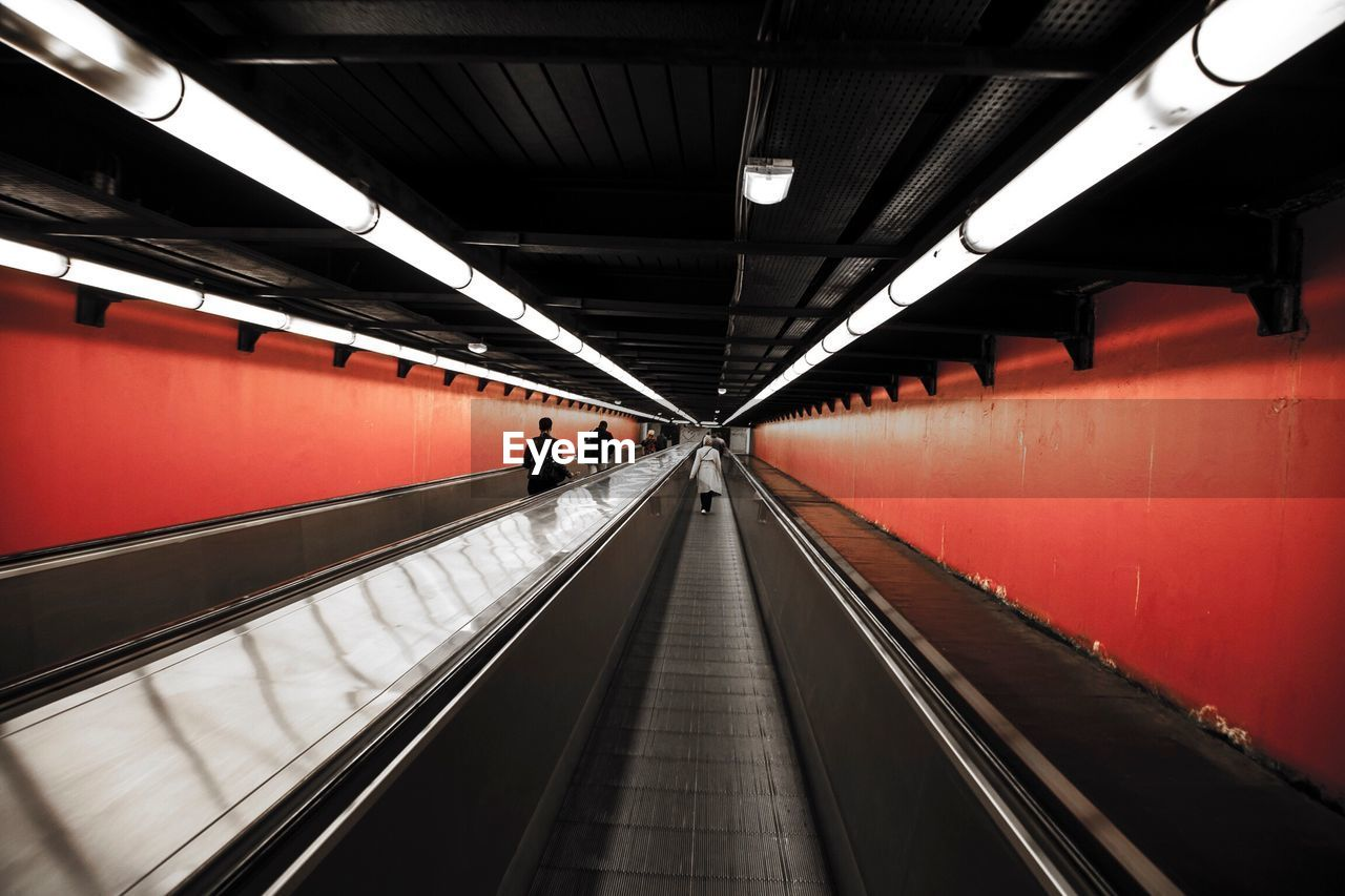 People On Moving Walkway In Subway Station