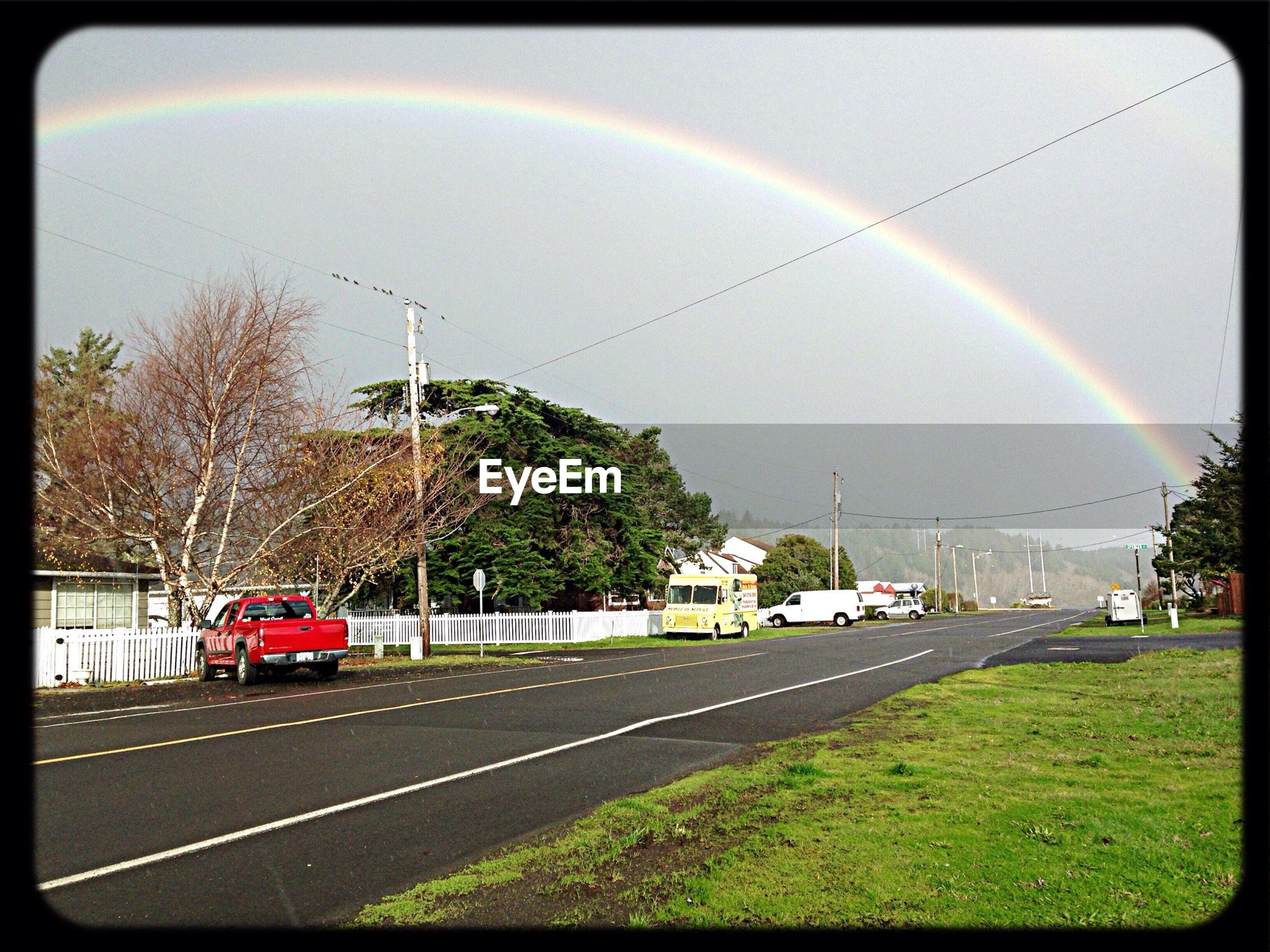 Road against rainbow in sky