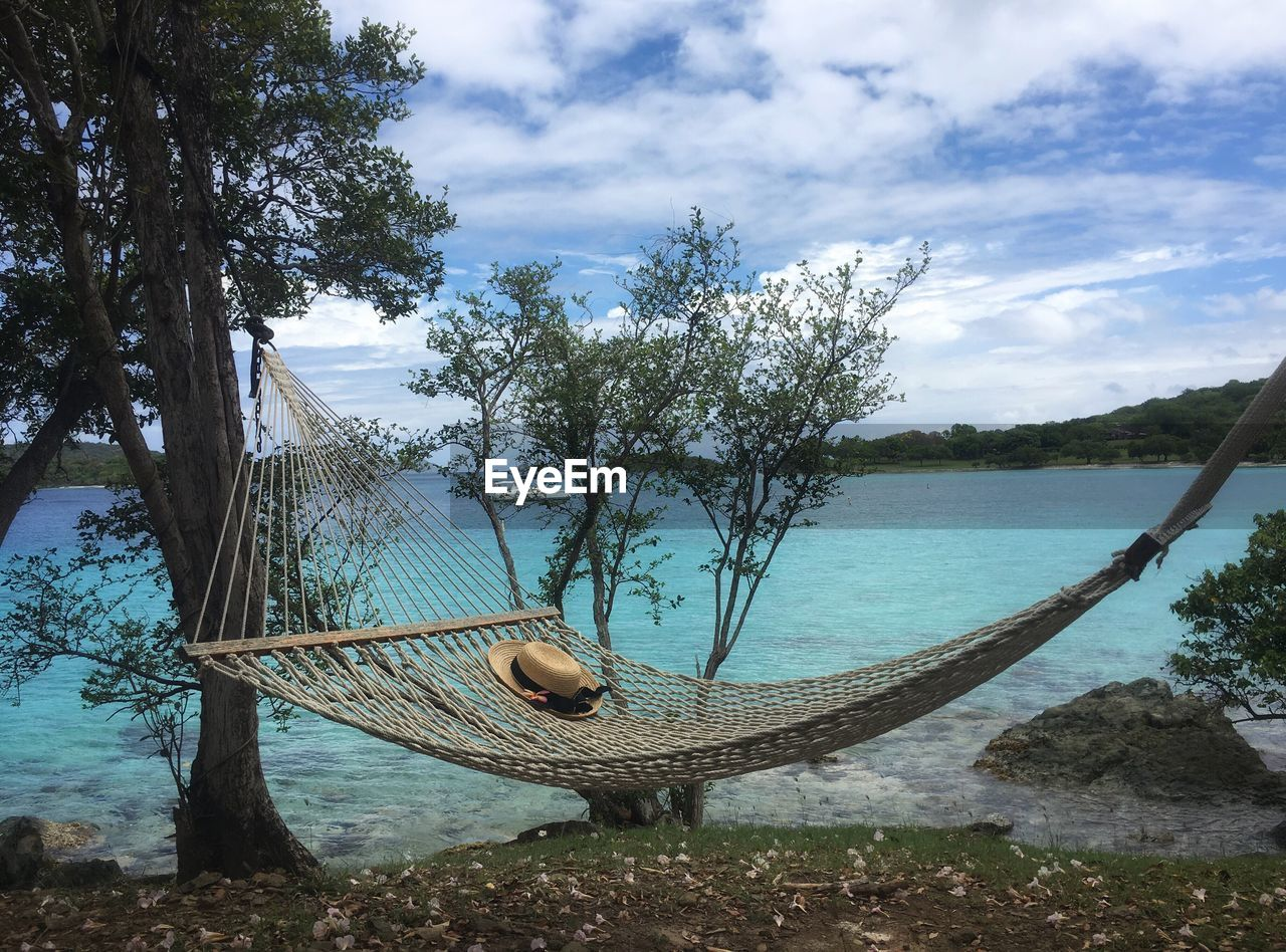 Hammock By Lake Against Cloudy Sky