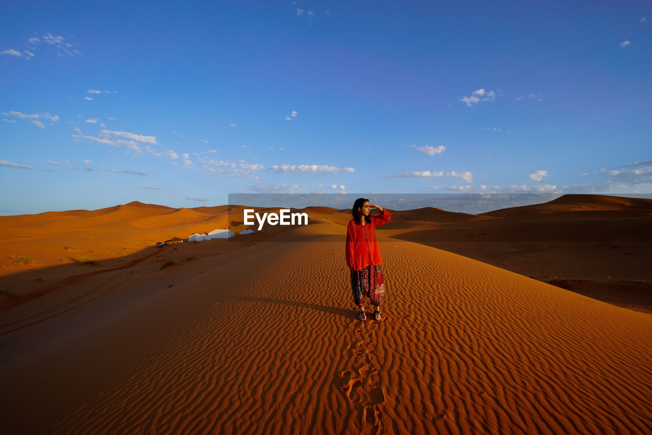 desert, sky, land, one person, real people, sand, landscape, scenics - nature, beauty in nature, non-urban scene, climate, sand dune, lifestyles, tranquil scene, nature, rear view, arid climate, environment, full length, tranquility, outdoors