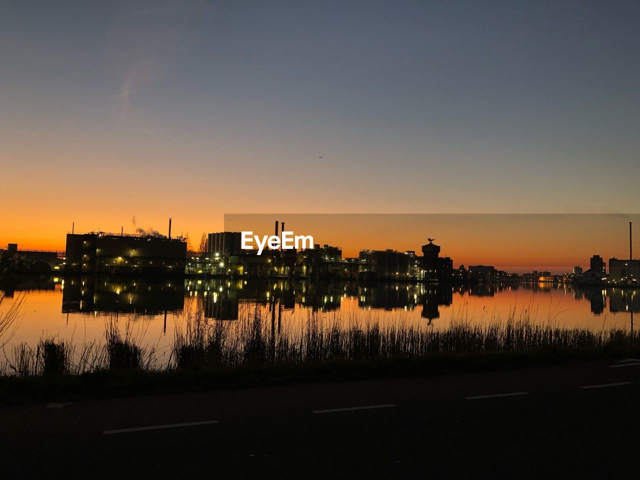 sky, water, sunset, reflection, nature, architecture, building exterior, no people, built structure, lake, orange color, industry, outdoors, factory, copy space, clear sky, waterfront, beauty in nature