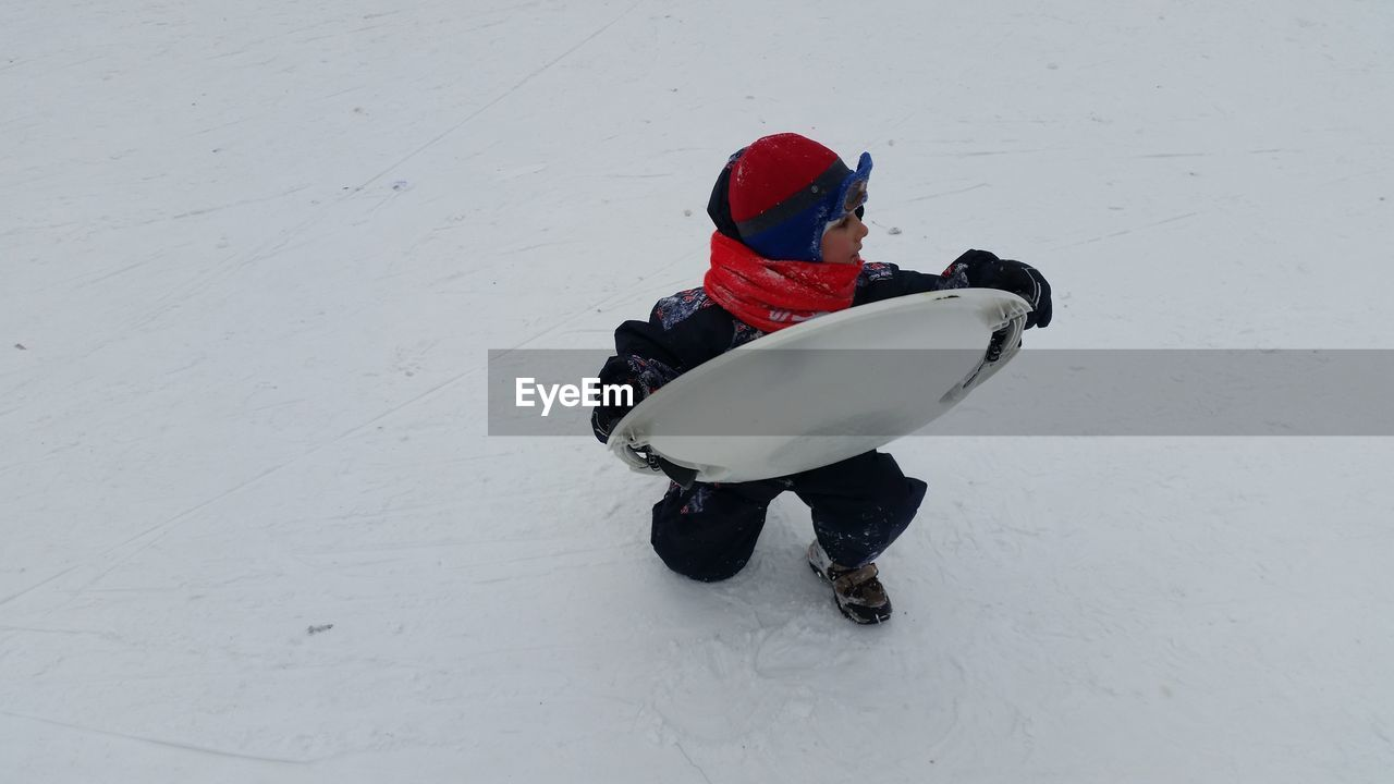 snow, winter, cold temperature, white color, field, warm clothing, sport, land, clothing, leisure activity, nature, child, real people, full length, high angle view, childhood, day, covering, winter sport, tobogganing
