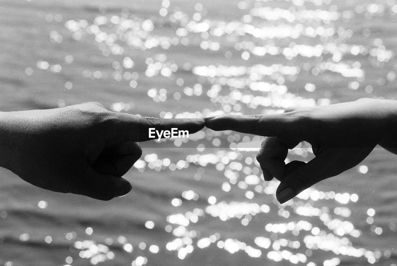 Cropped hands of couple touching fingers against sea