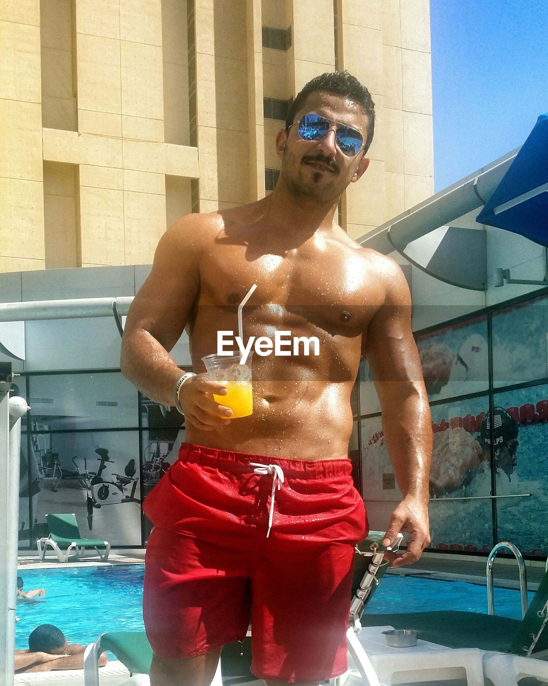 lifestyles, leisure activity, water, holding, built structure, architecture, swimming pool, men, person, building exterior, blue, casual clothing, refreshment, motion, glass - material, shirtless